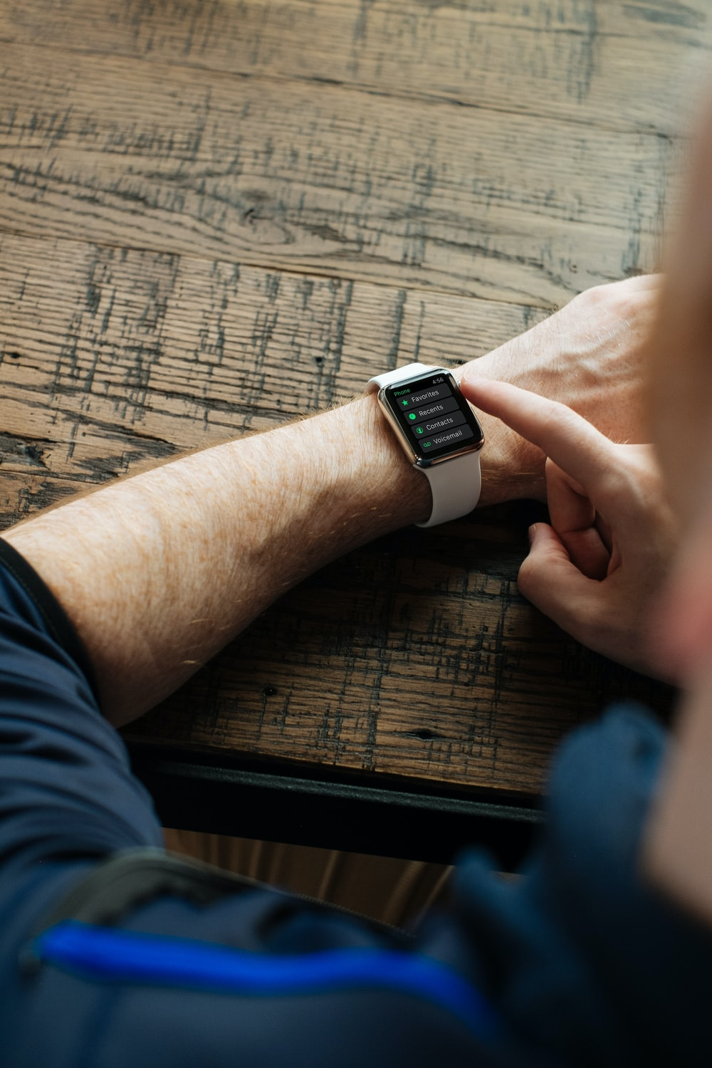 person wearing silver Apple Watch with white band