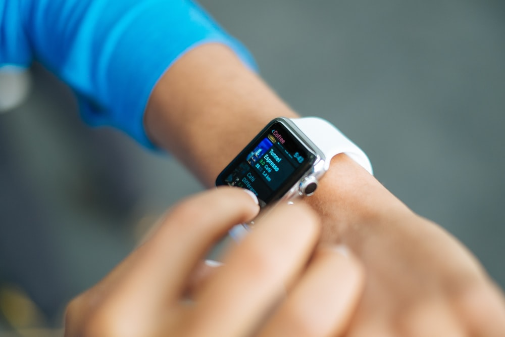 person wearing silver Apple Watch with white Sport Band