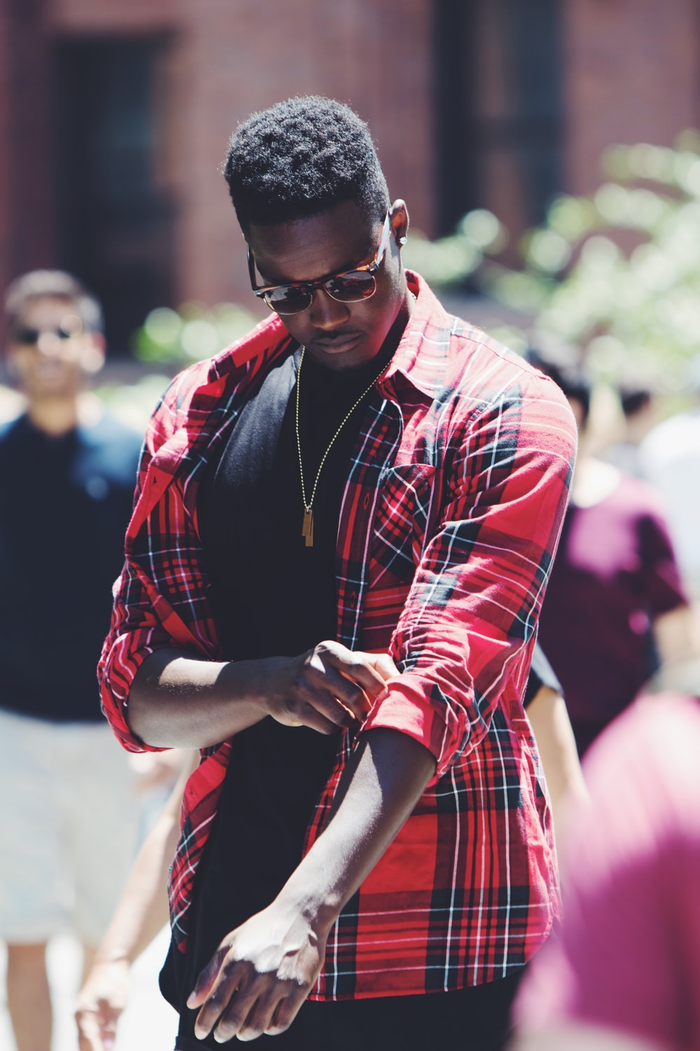 man fixing his red, black, and white plaid sport shirt sleeve during daytime