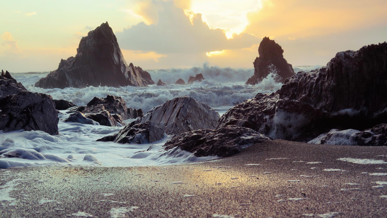 violent waves splashing into rocky coastline during daytime