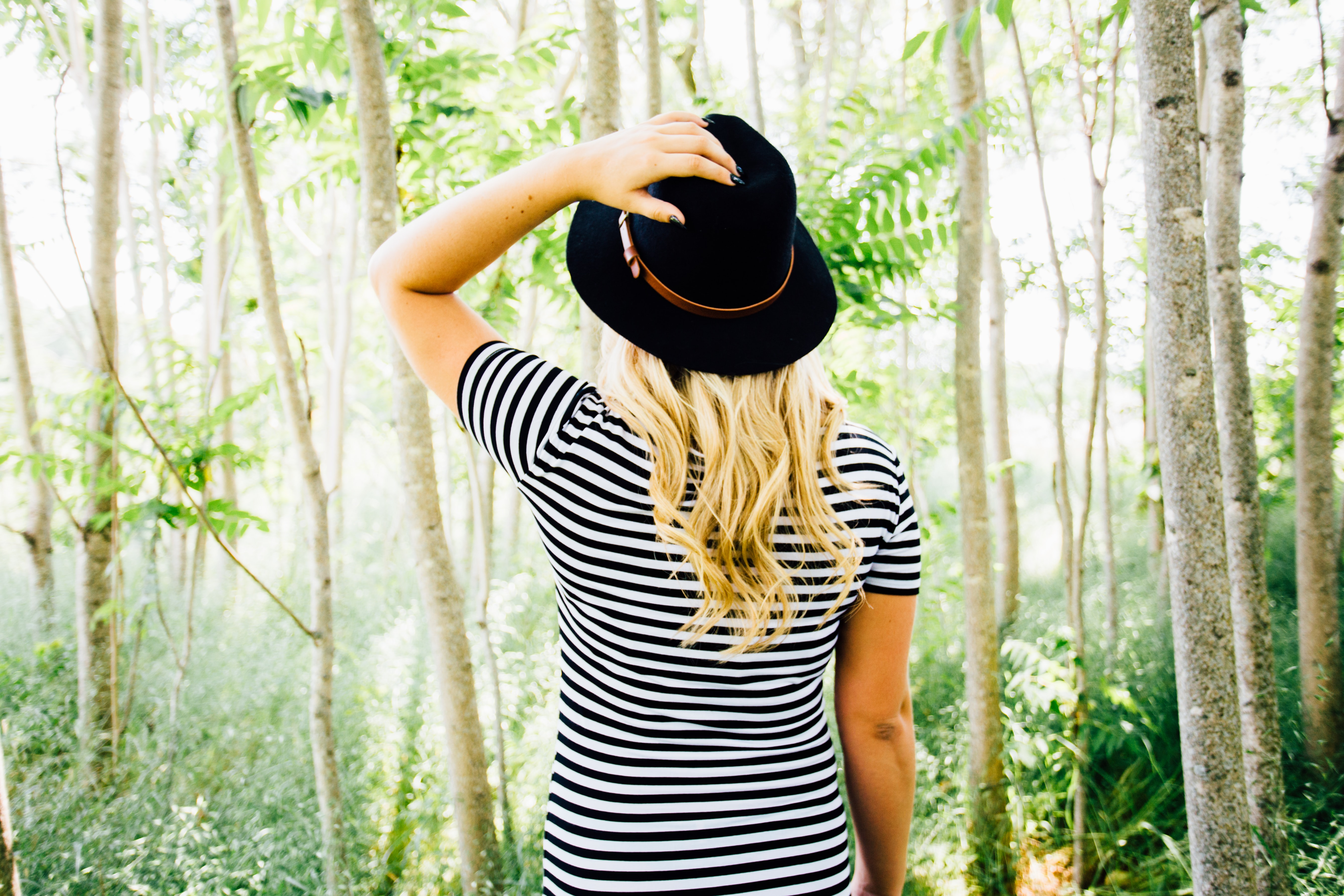 A blonde woman in a black hat standing back to camera in a forest