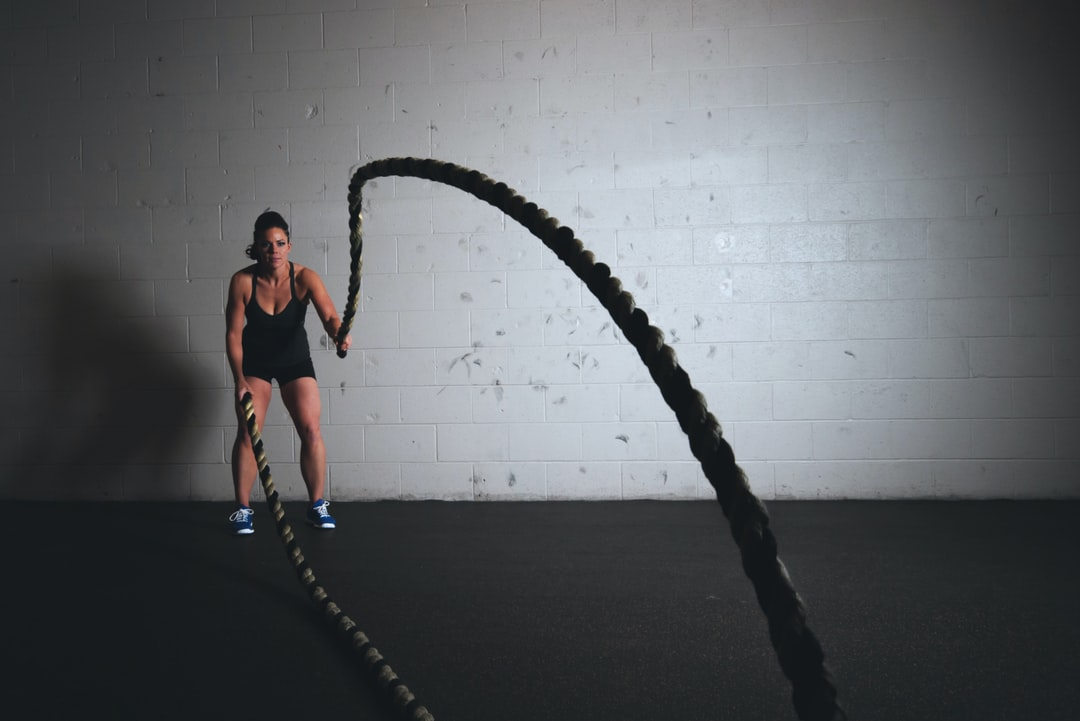 Woman working out with battle ropes and getting fit!