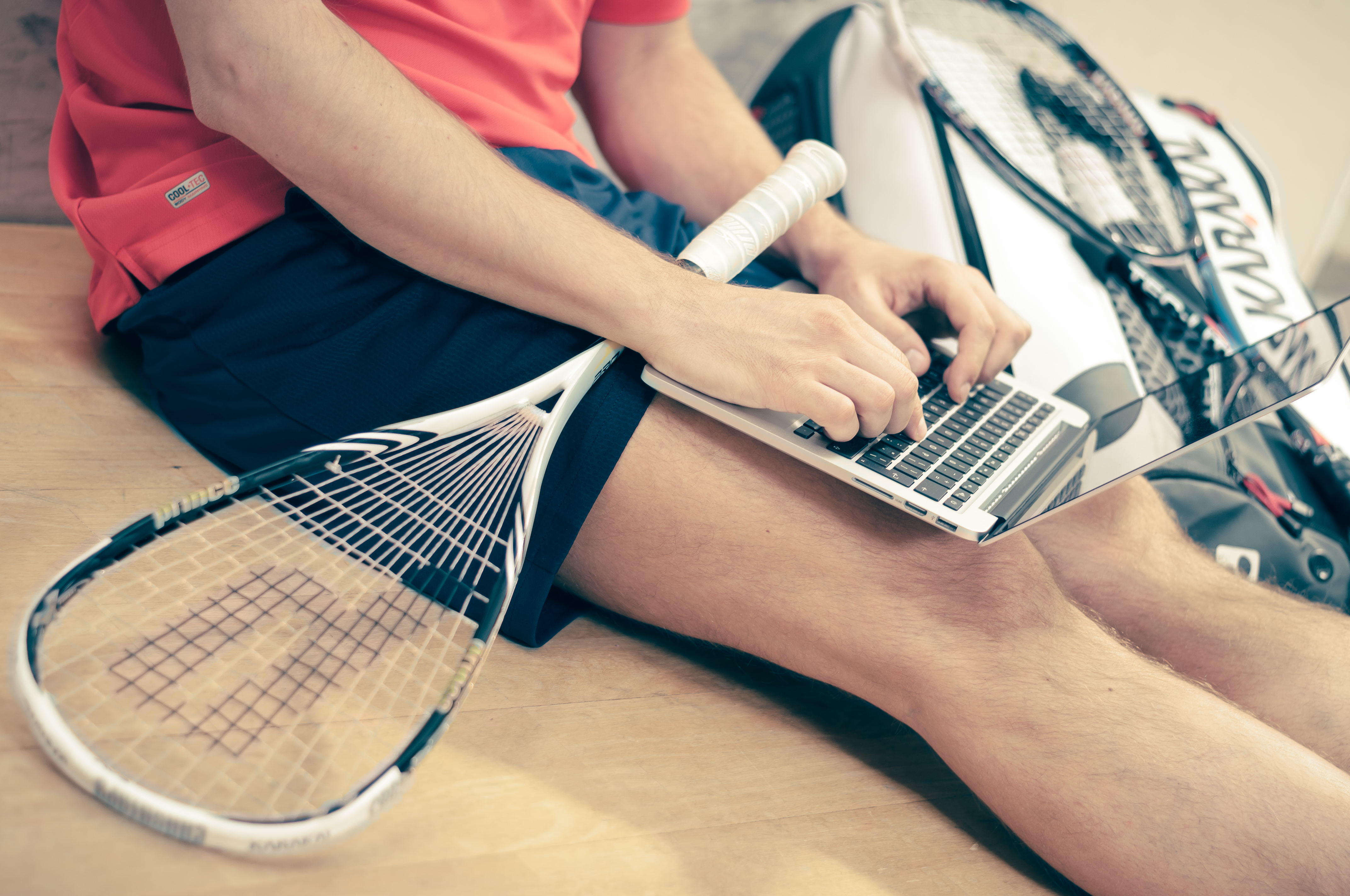 A man with a tennis racket on his lap working on a laptop