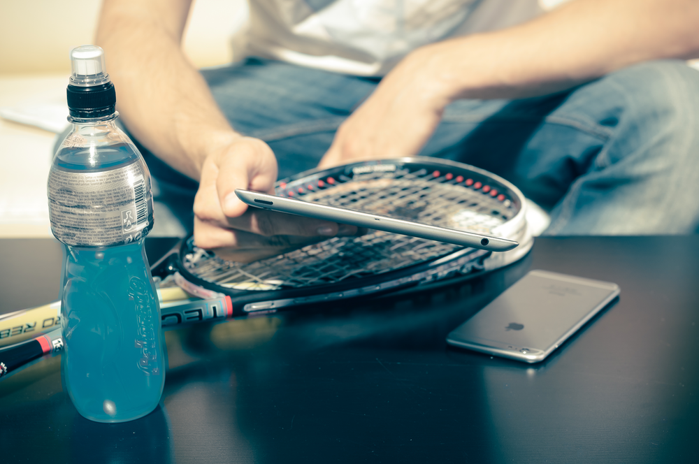 person sitting while using iPhone 8 and tennis racket beside energy drink bottle