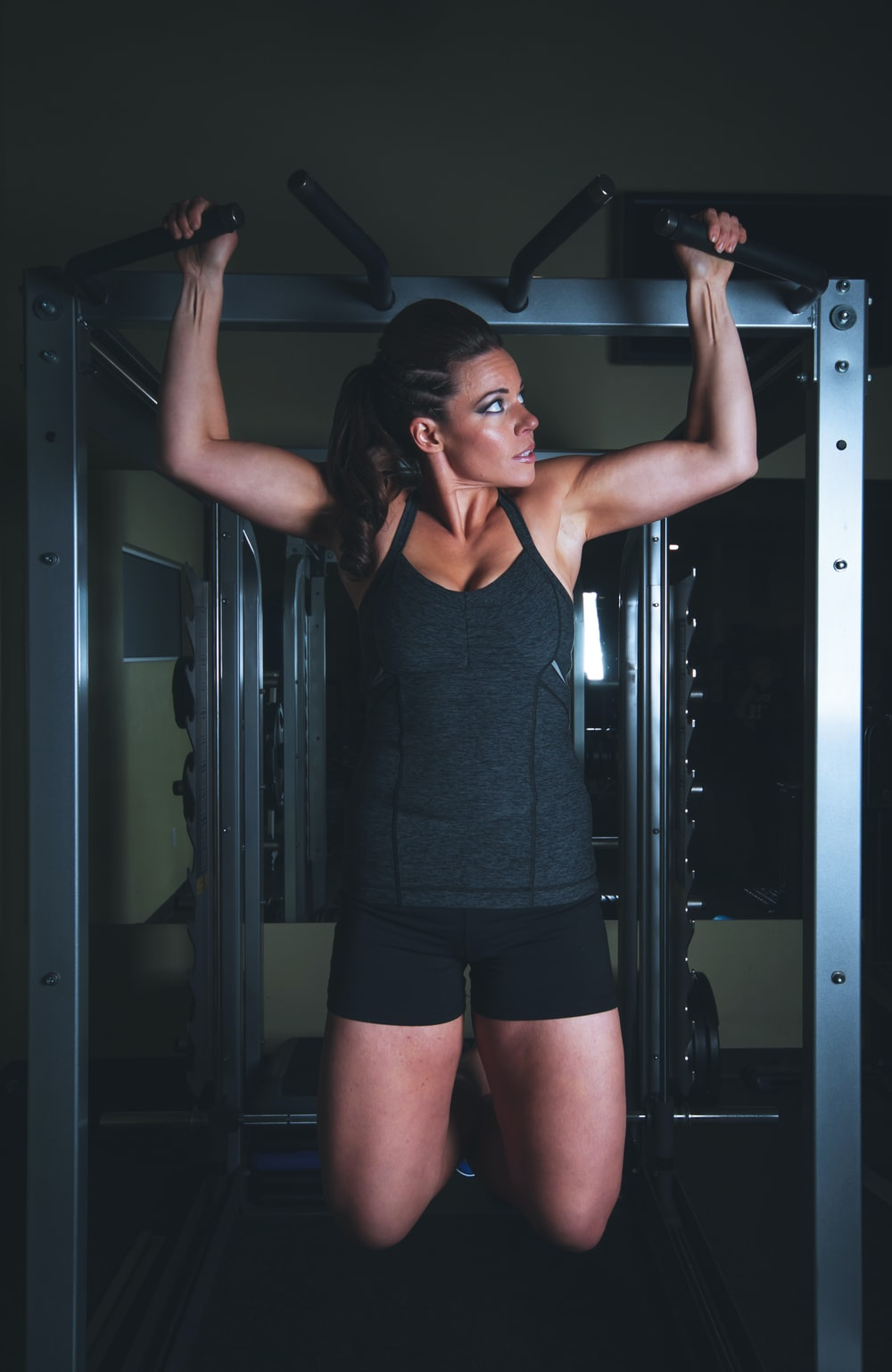 A woman doing a pull up at the gym for bodybuilding training
