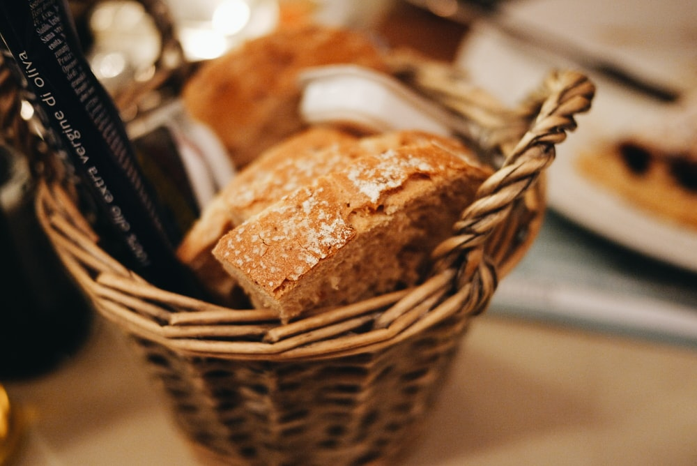 selective focus photography of baked bread on wicker basket