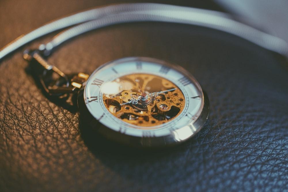 round silver-colored frame skeleton pocket watch