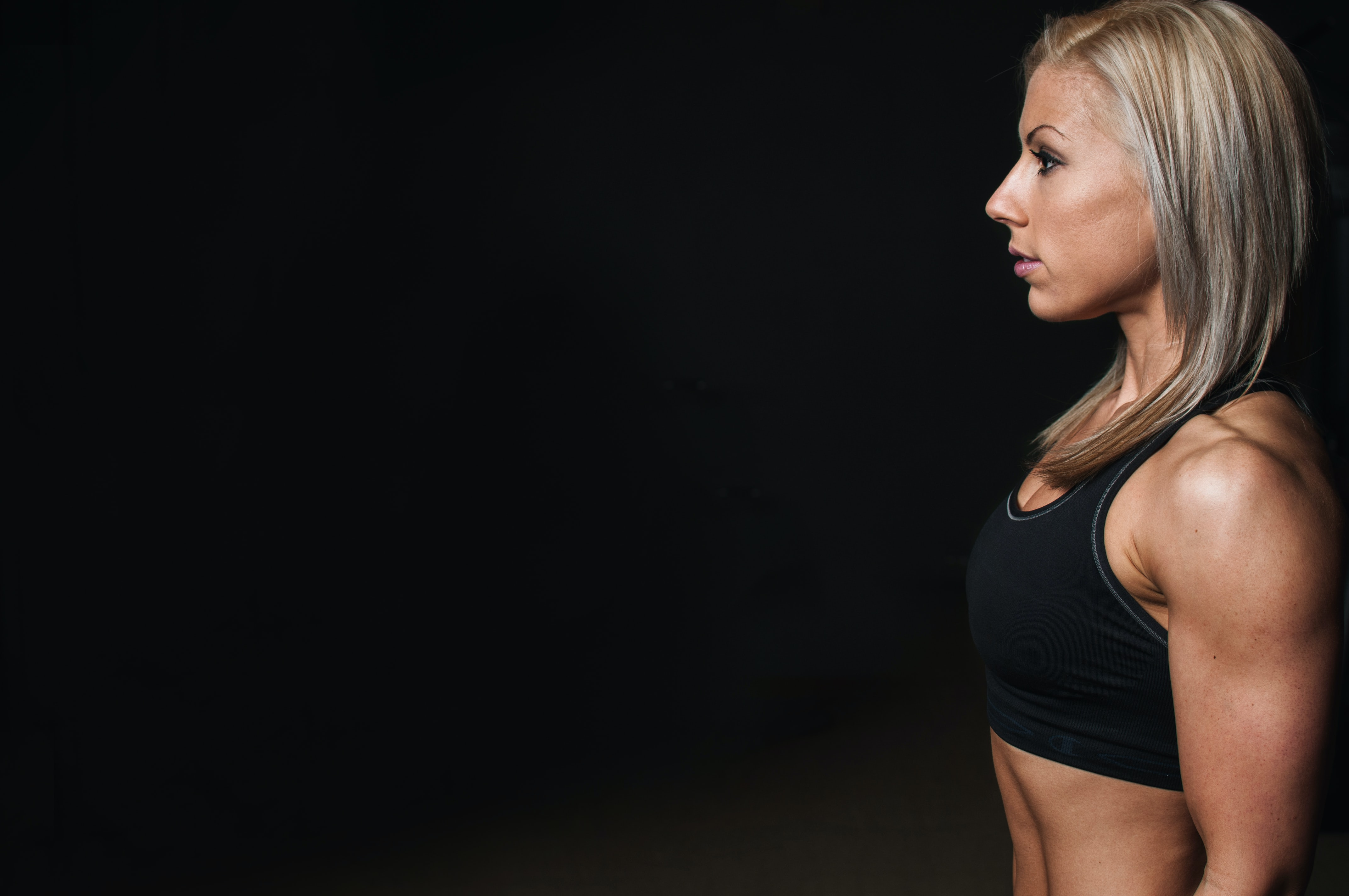 A fit blonde woman wearing a black sports bra at World Gym