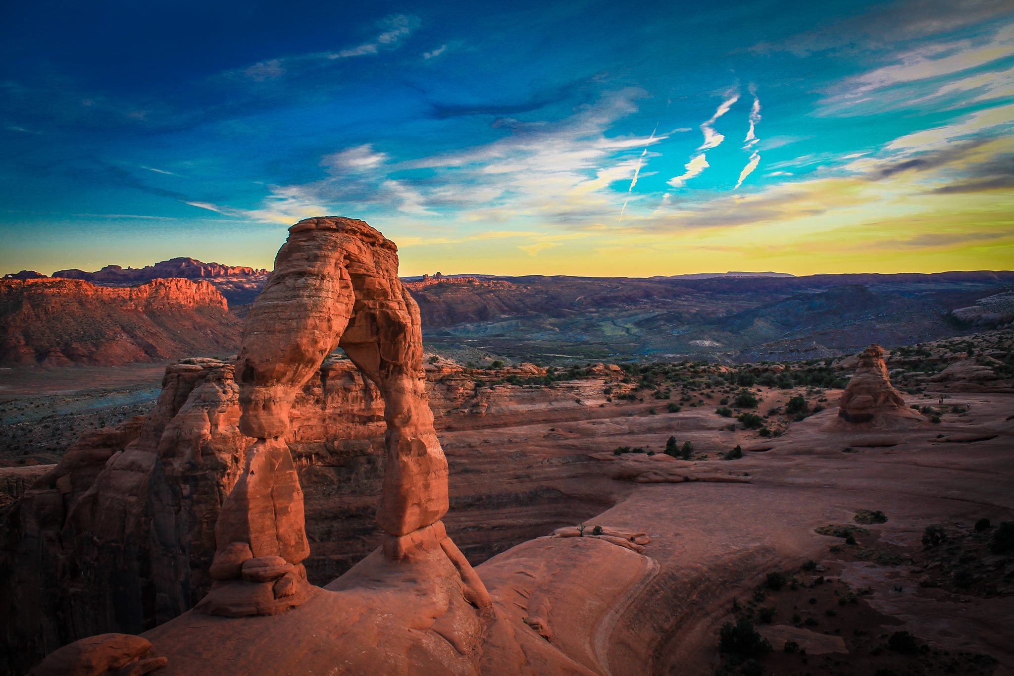 Natural canyon arch in a desert with a colorful sky in the background