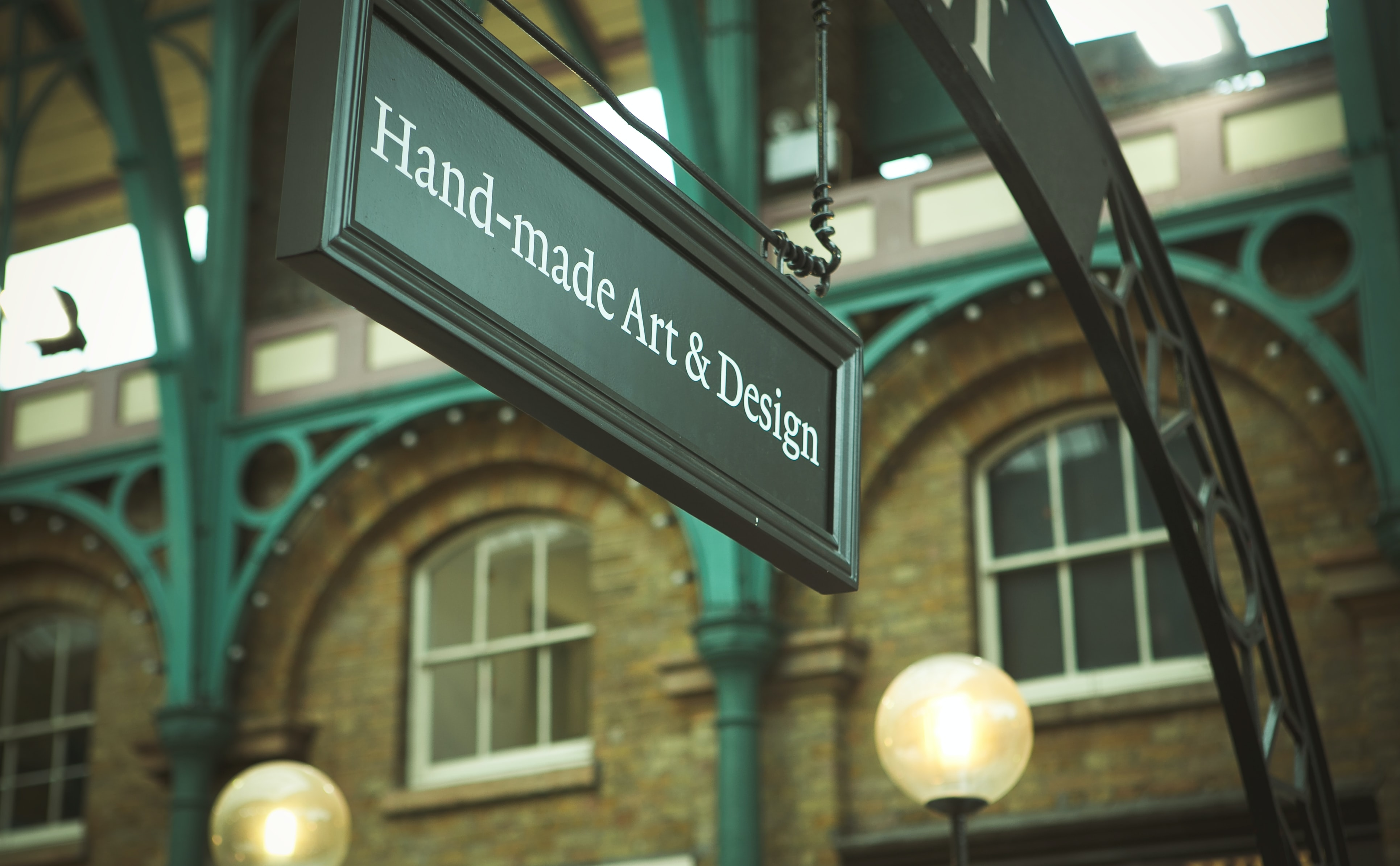Black hand-made art & design sign with brick walls in Covent Garden, London