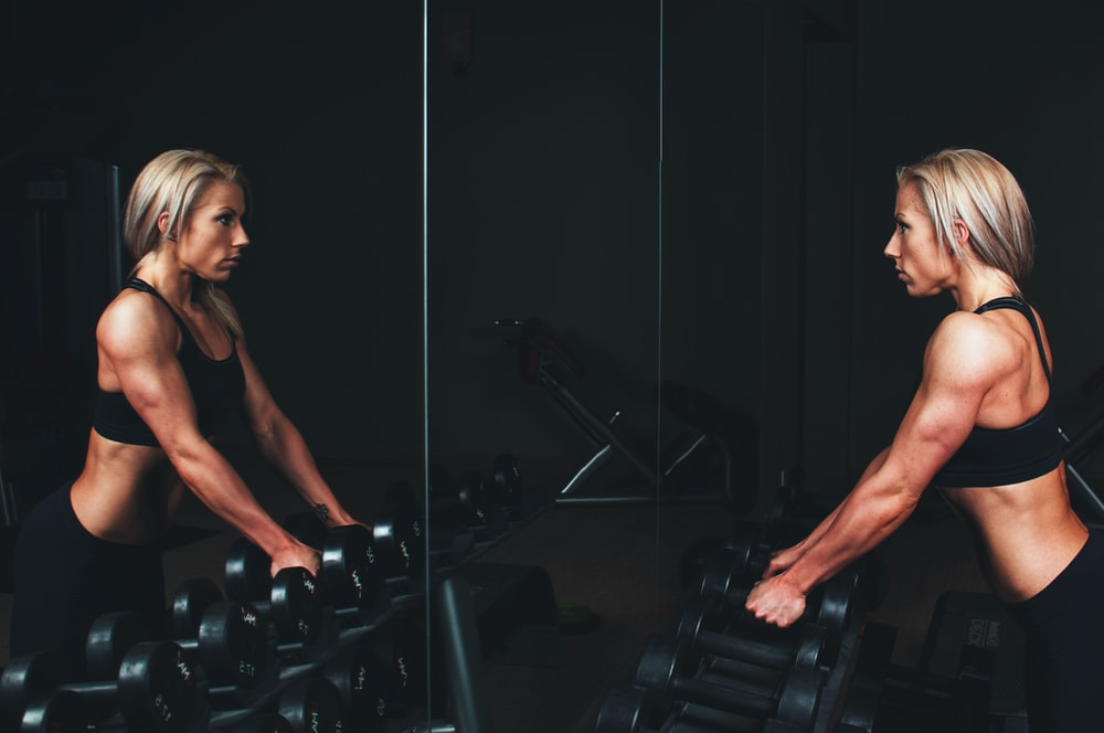 woman wearing black top top holding black dumbbells standing in front of mirror