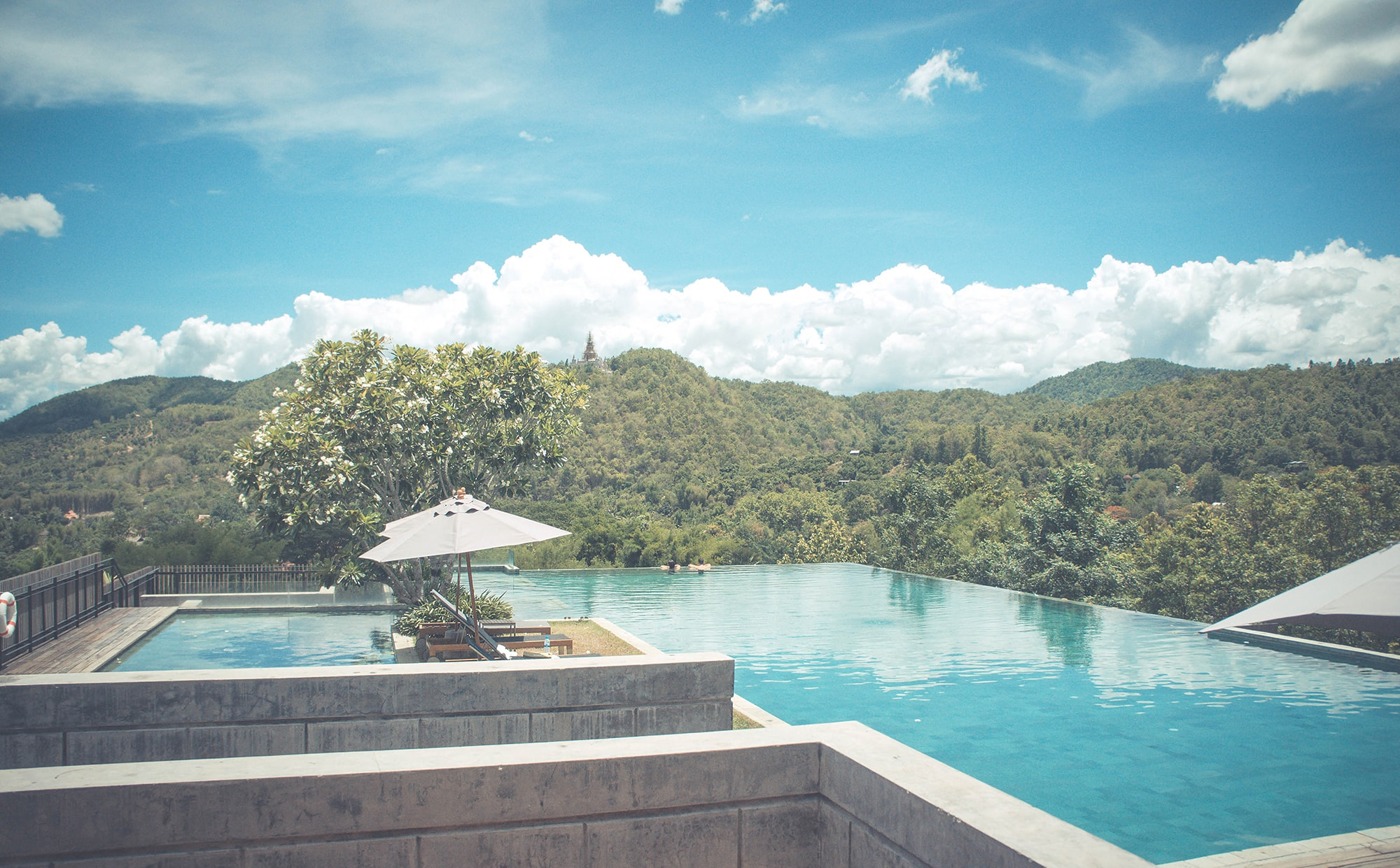 A large sunlit pool with a view on wooded hills