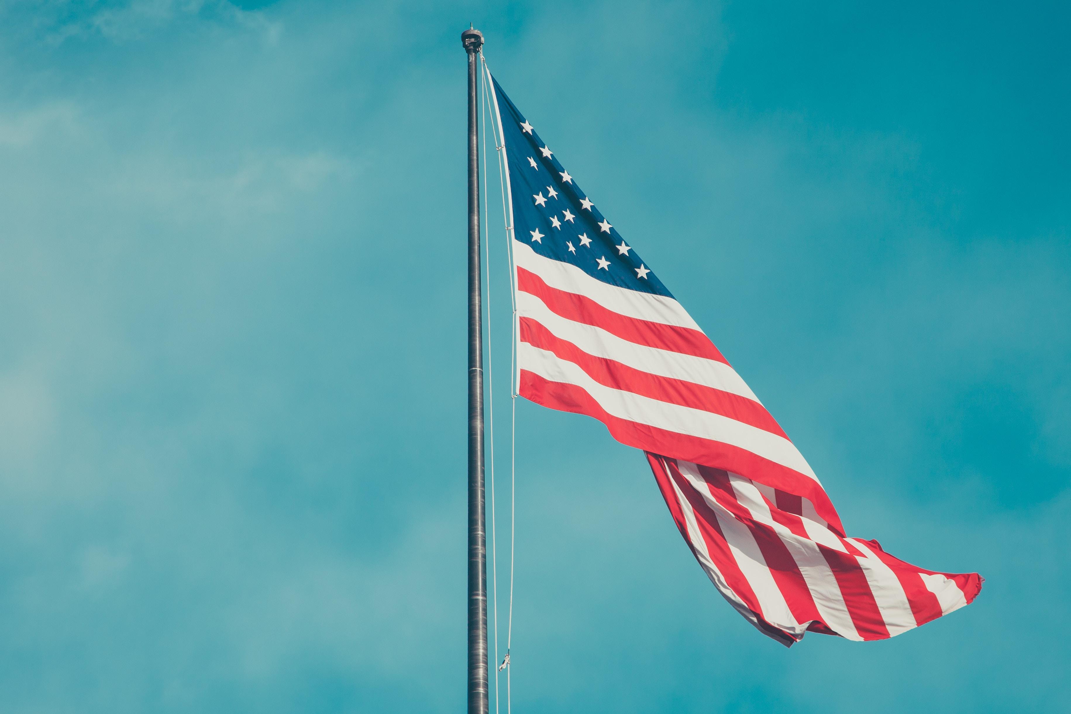 raised USA flag under blue sky