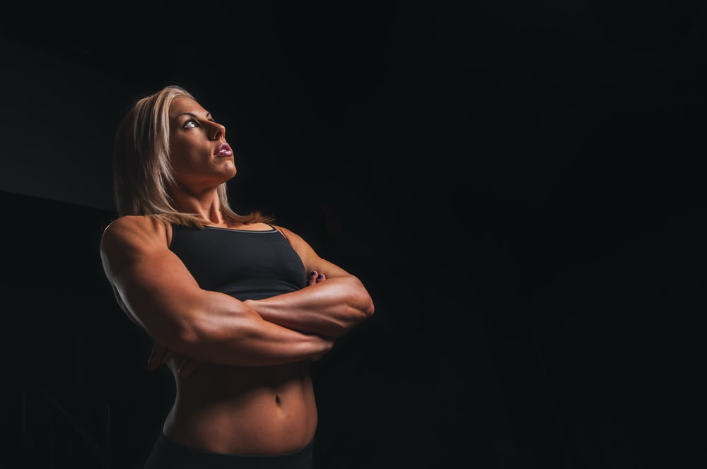 A tanned, muscular woman wearing a sports bra standing tall