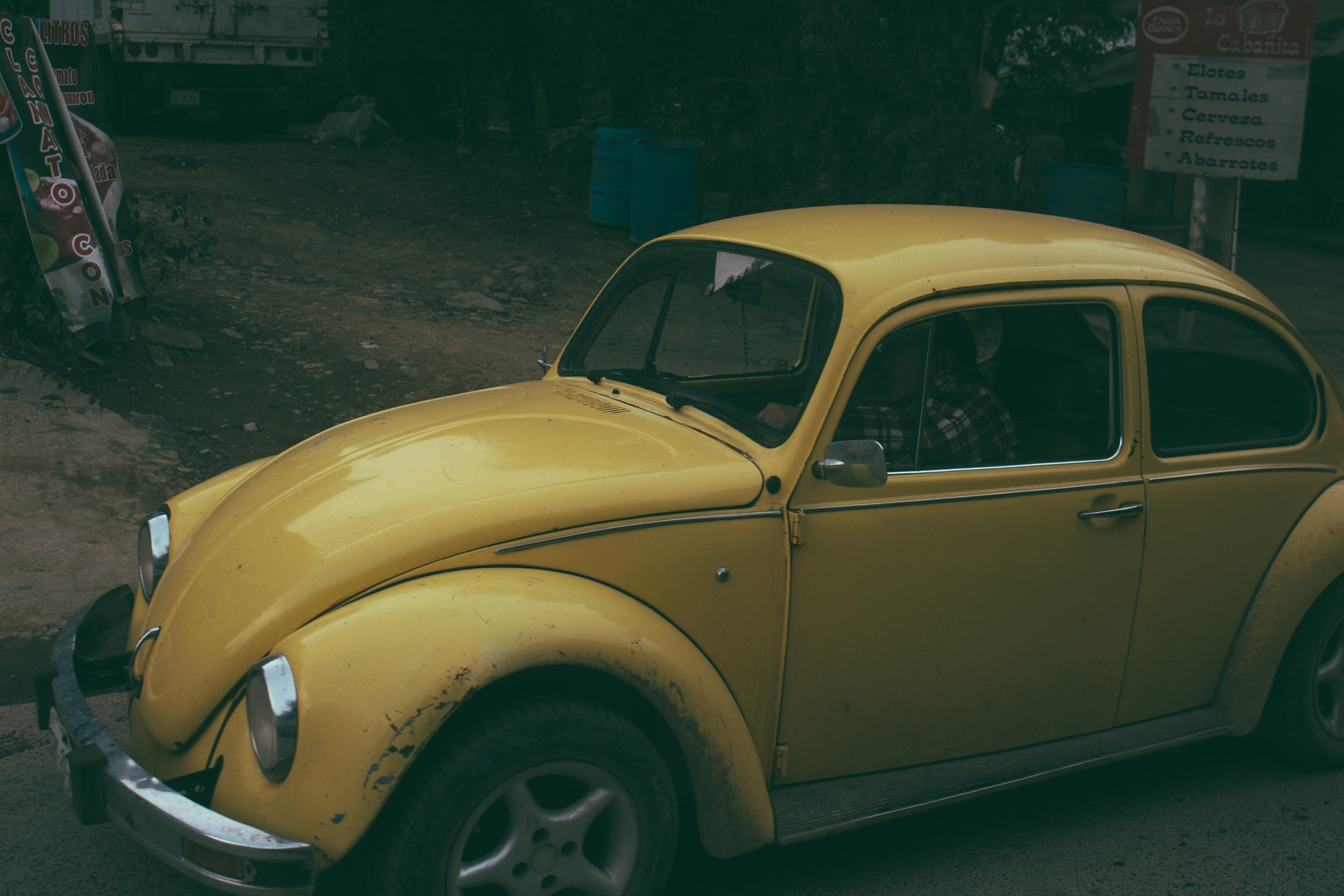 Underexposed shot of a vintage yellow Volkswagen Beetle.