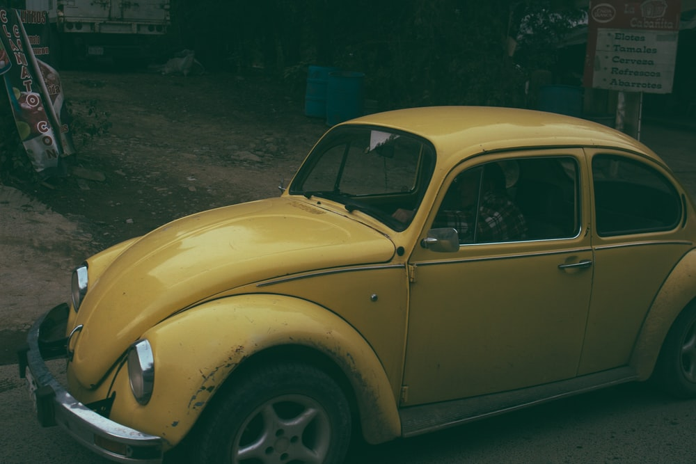 yellow Volkswagen Beetle coupe parked near white signage