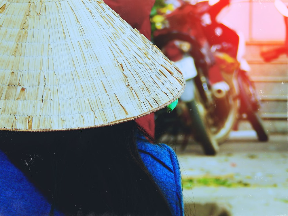 person wearing rice hat facing white motorcycle parked beside red wall