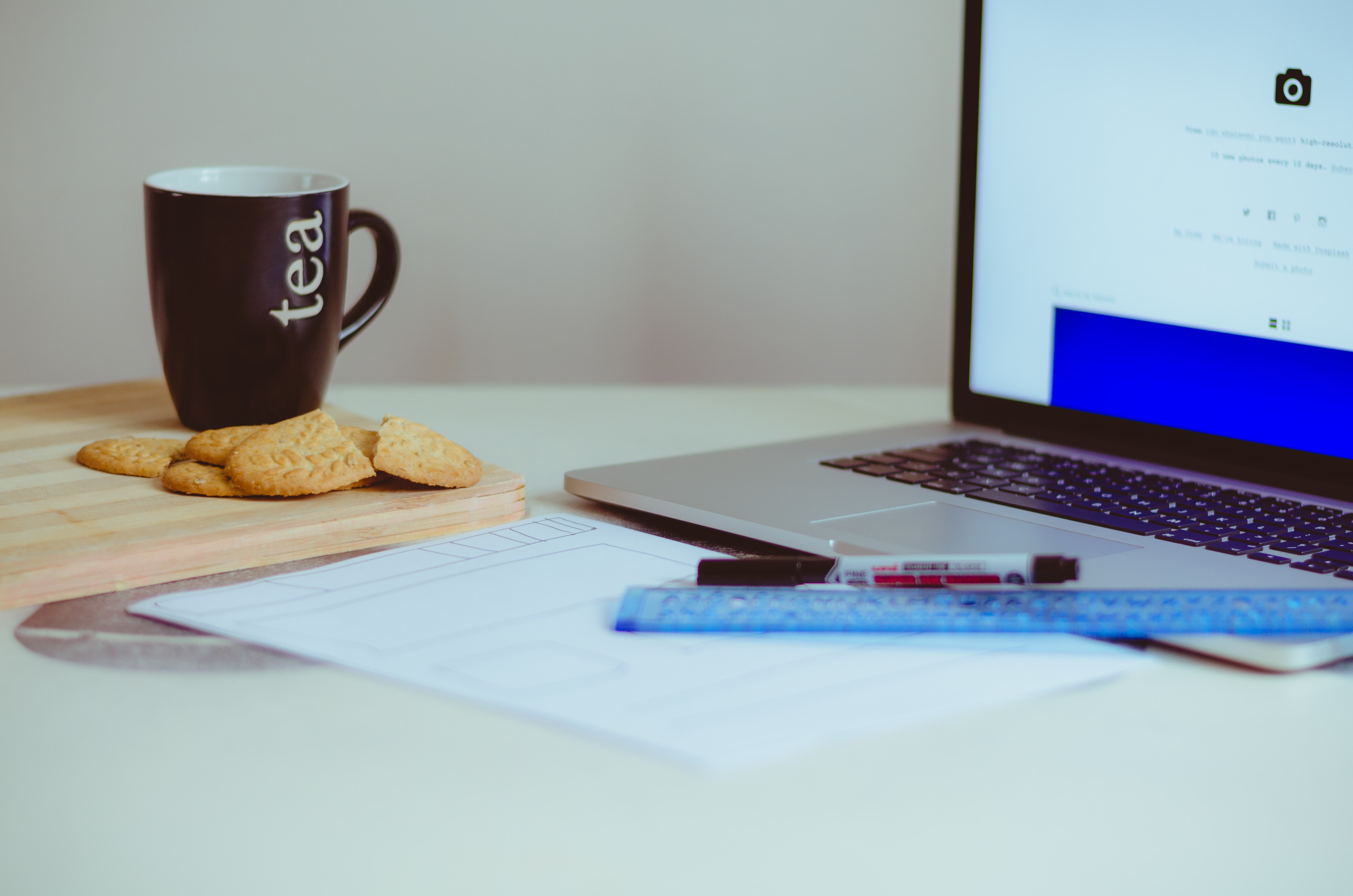 Tea and cookies on a wooden board near a laptop on a white workspace