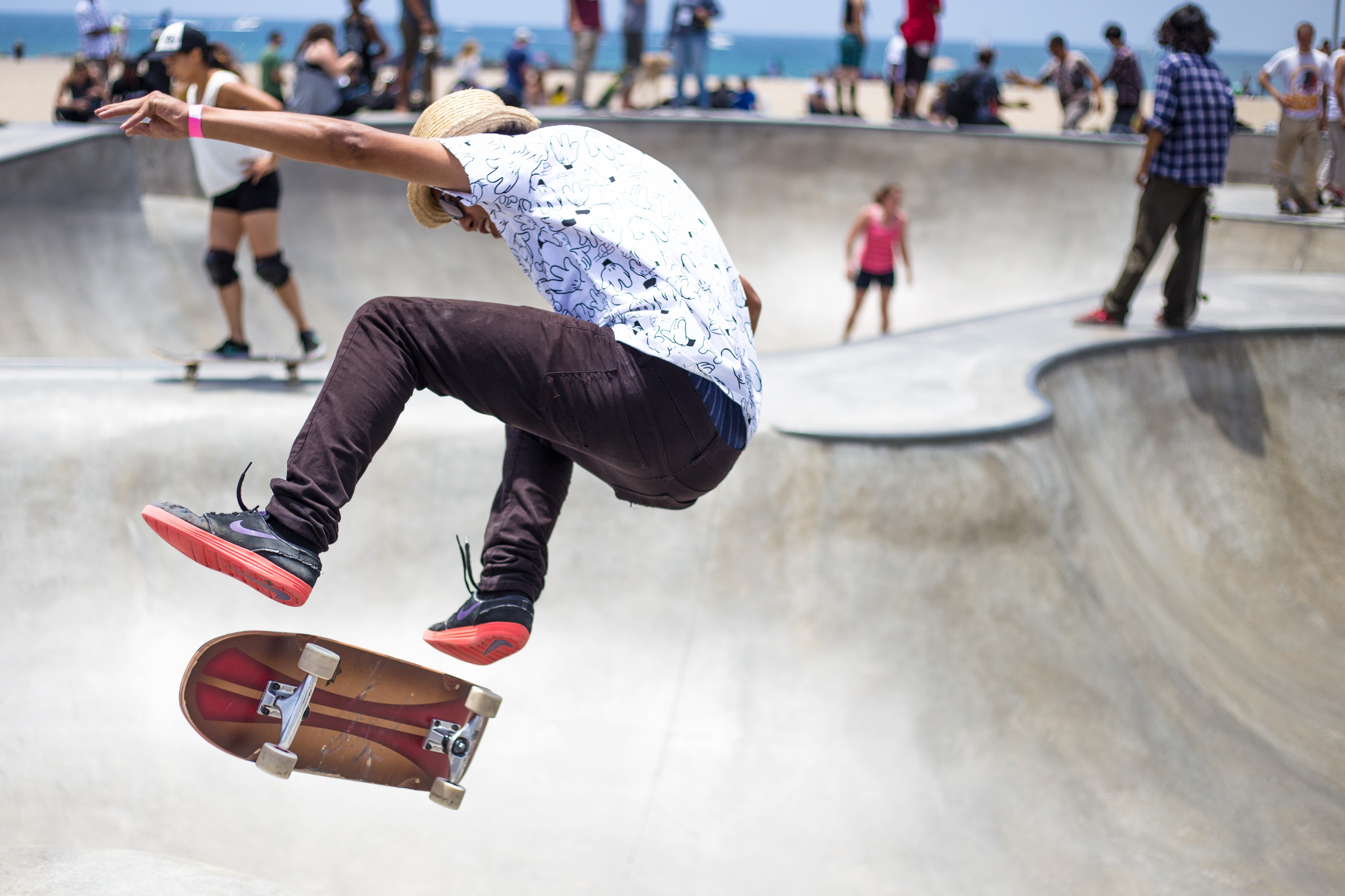 A man wearing a white shirt and hat doing tricks on a skateboard at a skatepark
