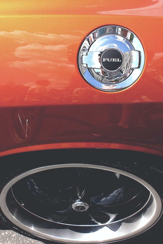 The fuel tank cap on an orange car.