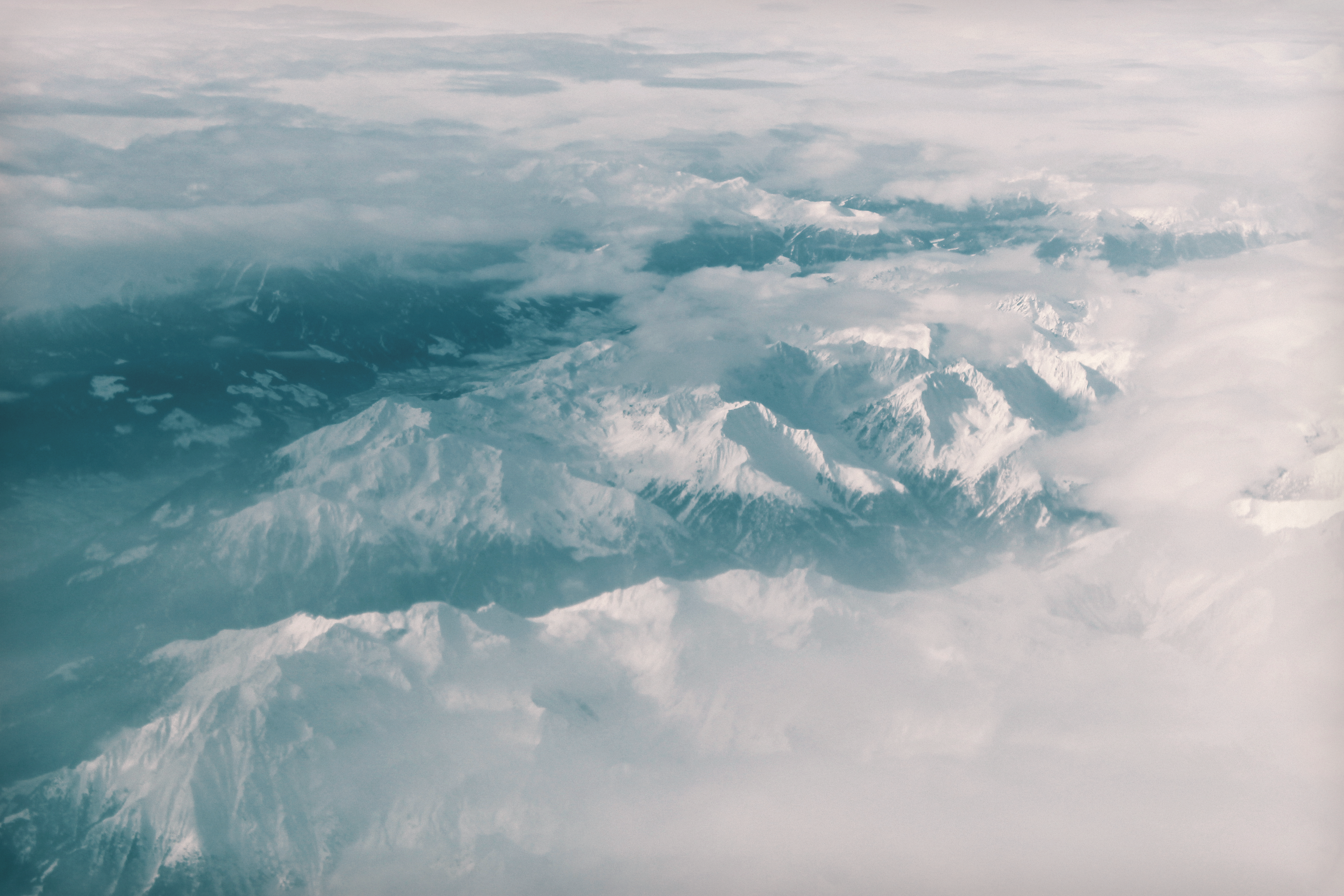 A drone view of the Swiss Alps' snow covered mountains surrounded by fog.