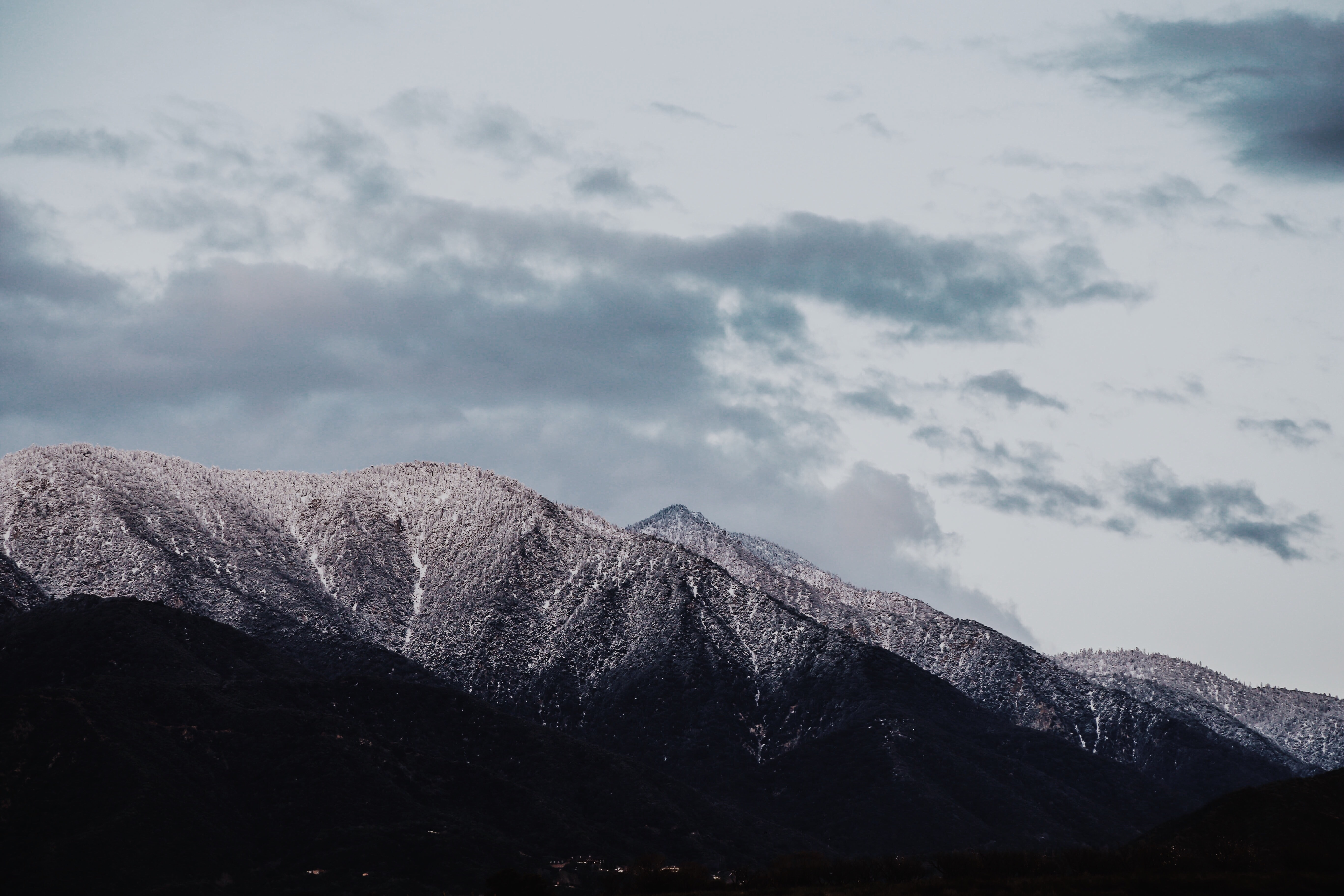 Light illuminates the snow on the mountain's peaks on an overcast day