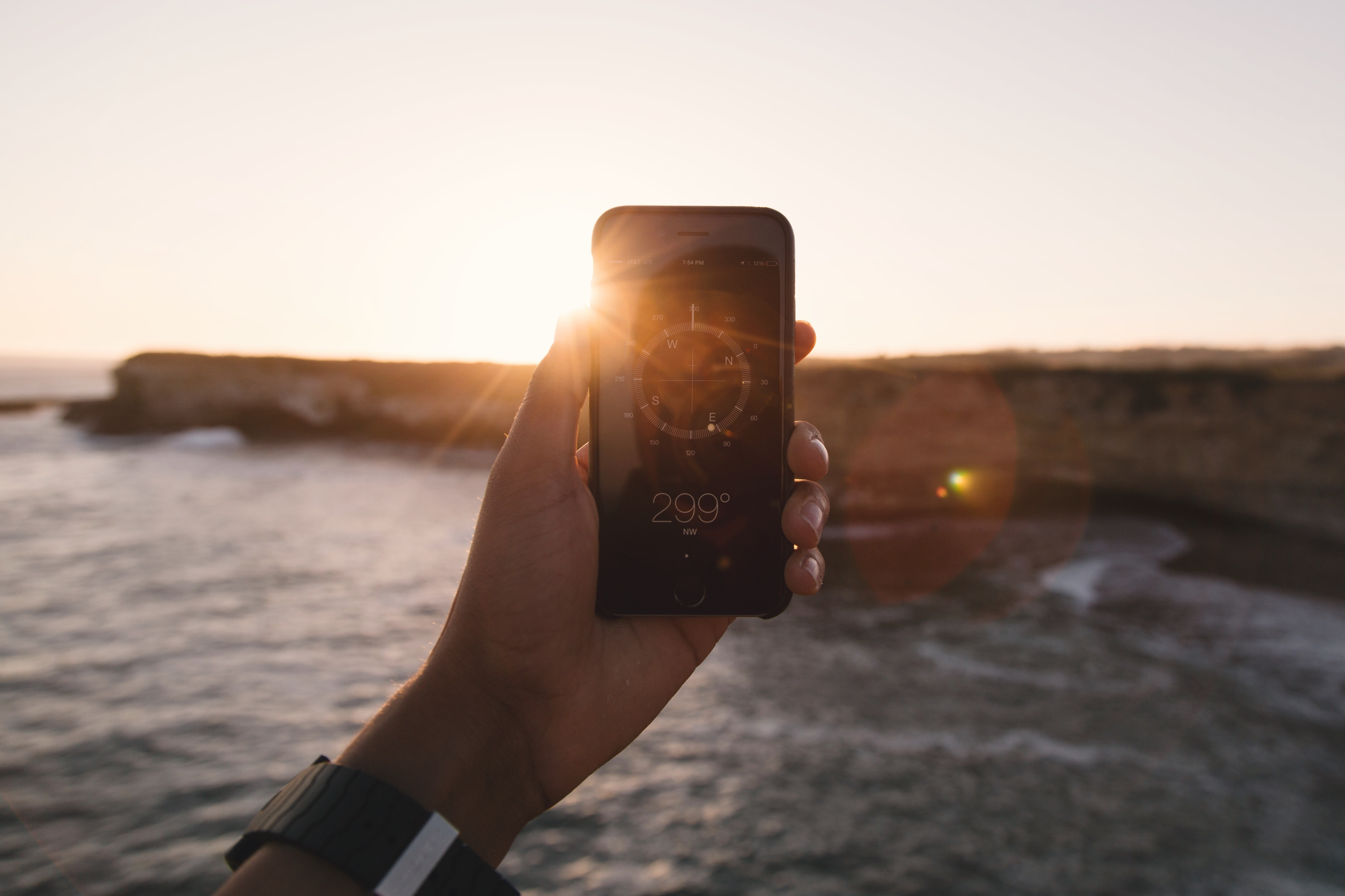 person holding black phone beside body of water under white sky during golden hour