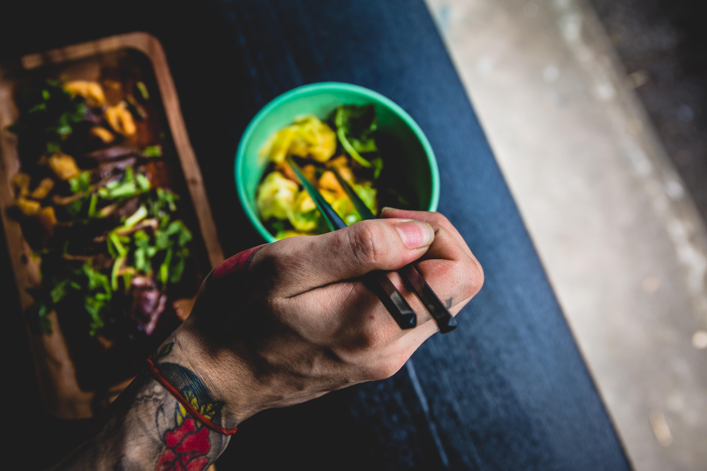 person holding chopsticks near green bowl