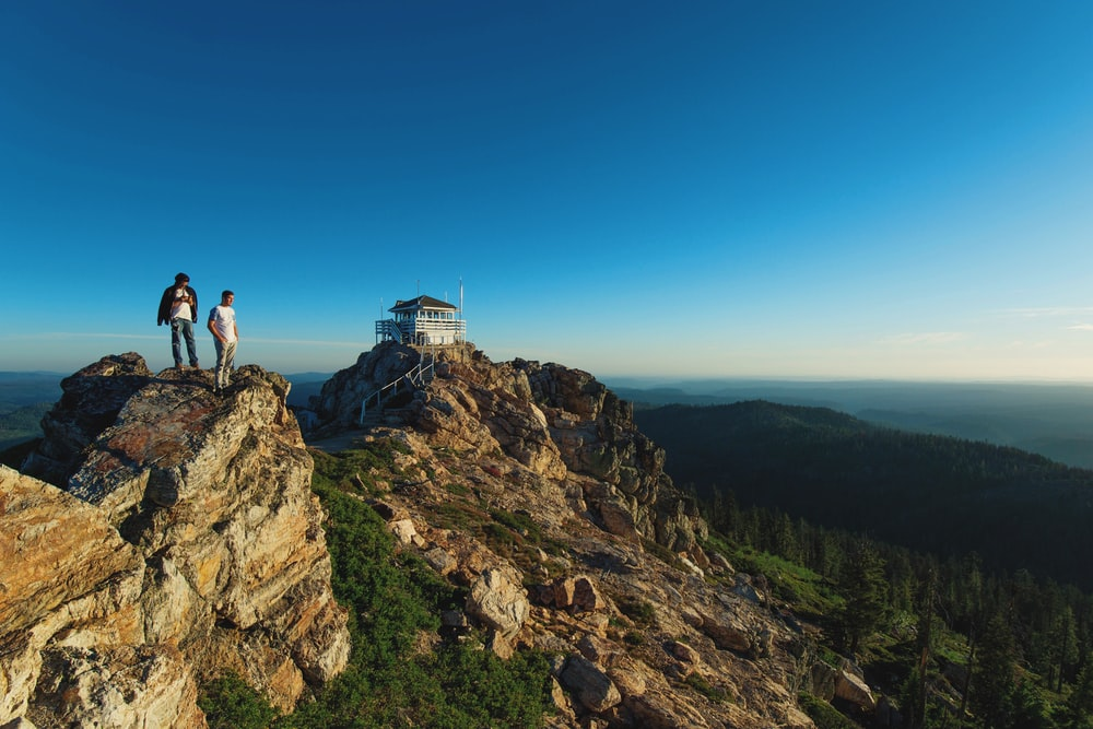 two men standing on rock formation