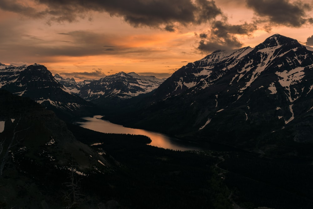 body of water surrounded by black and white mountains under gray sky at golden hour