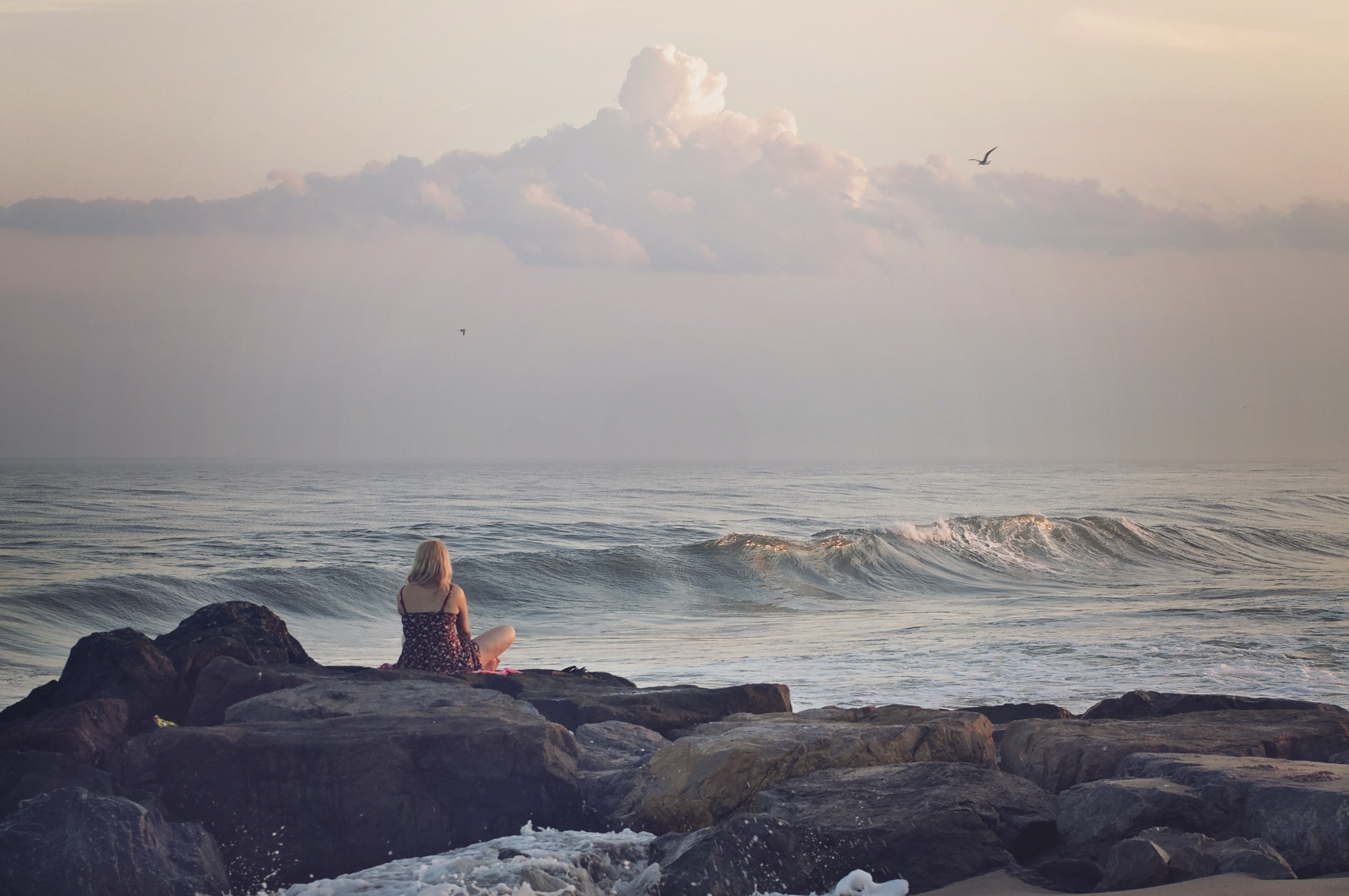 Woman sitting on the rock looking at the ocean waves at sunset