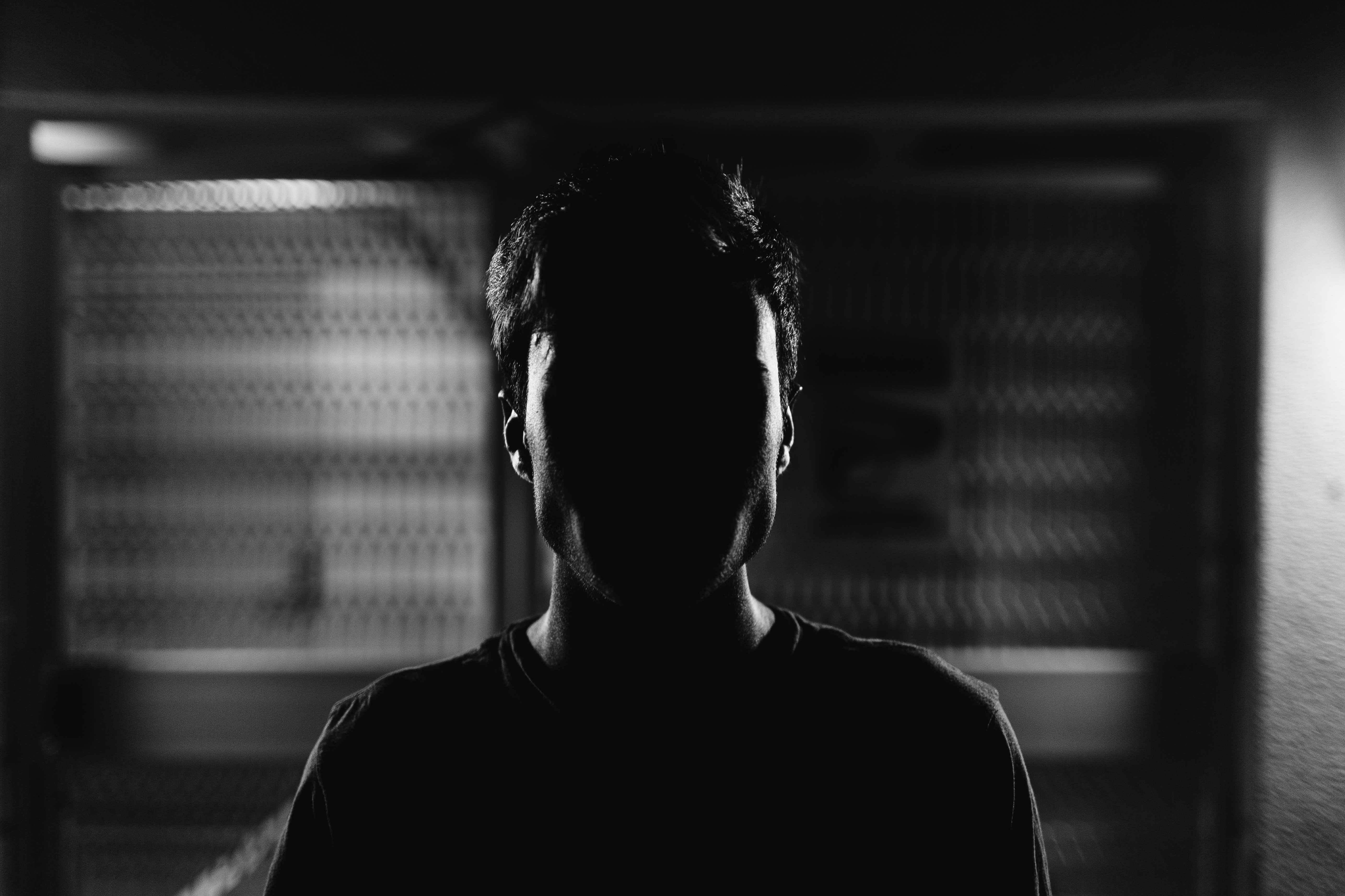 Black and white shot of young man with face obscured by shadow