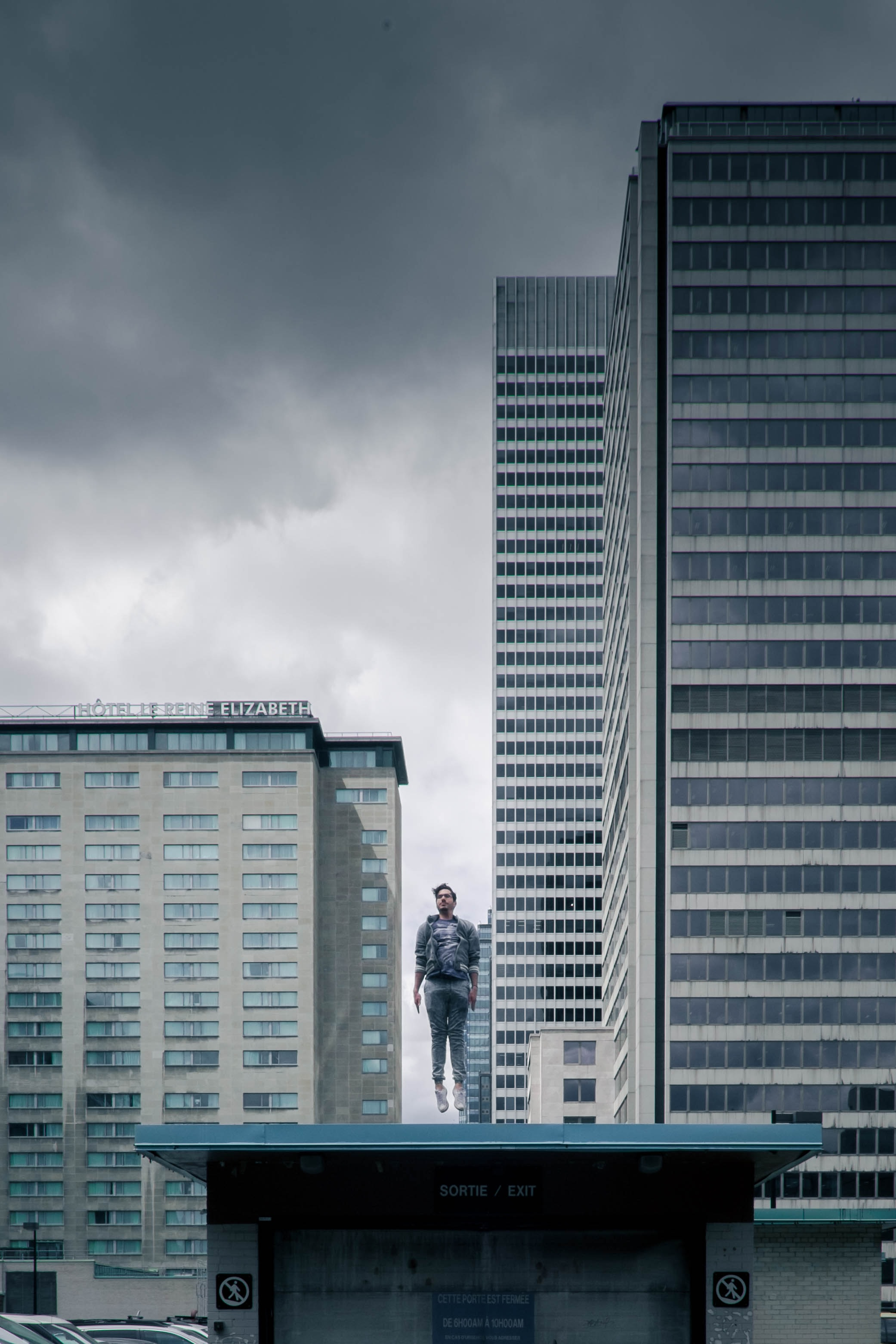 A blurry man standing on top of an urban skyscraper intends to jump