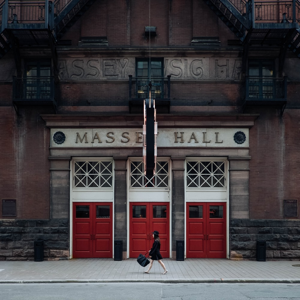 woman walking on street near red Masse Hall during daytime