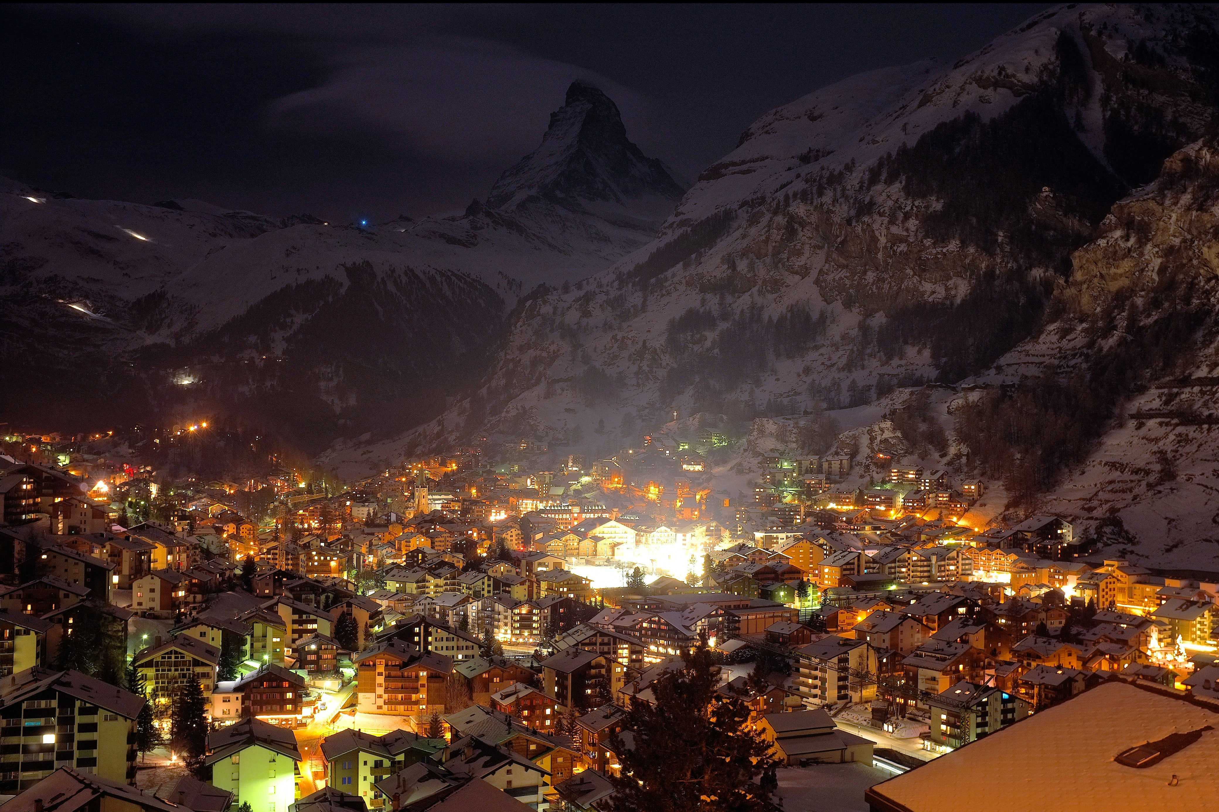 A village at night with all buildings lit up with a snow-covered mountain in the background