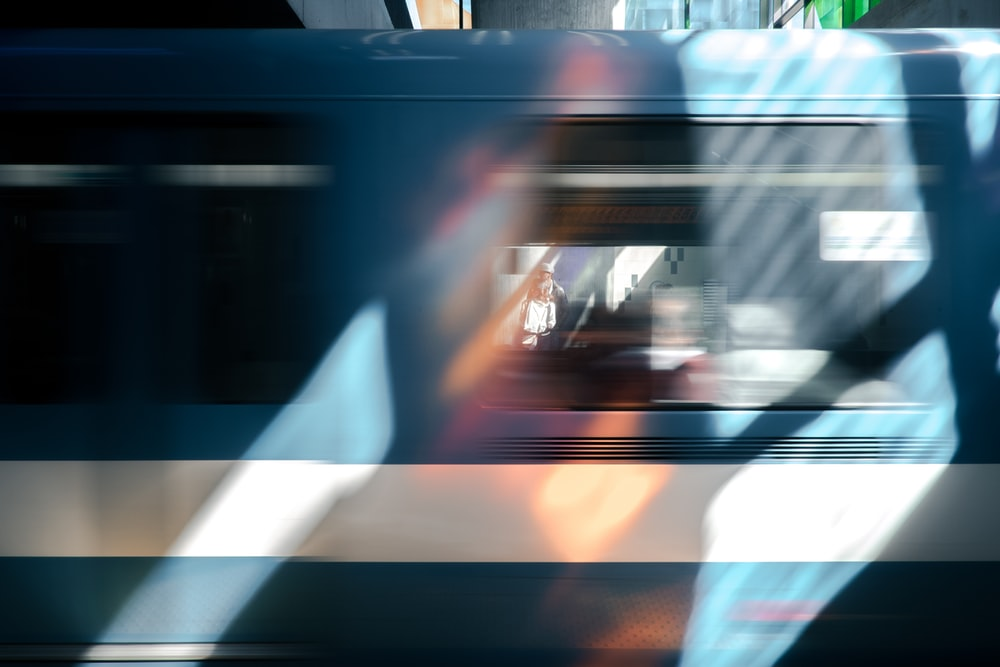 A blue train car blurring past briefly framing a person waiting