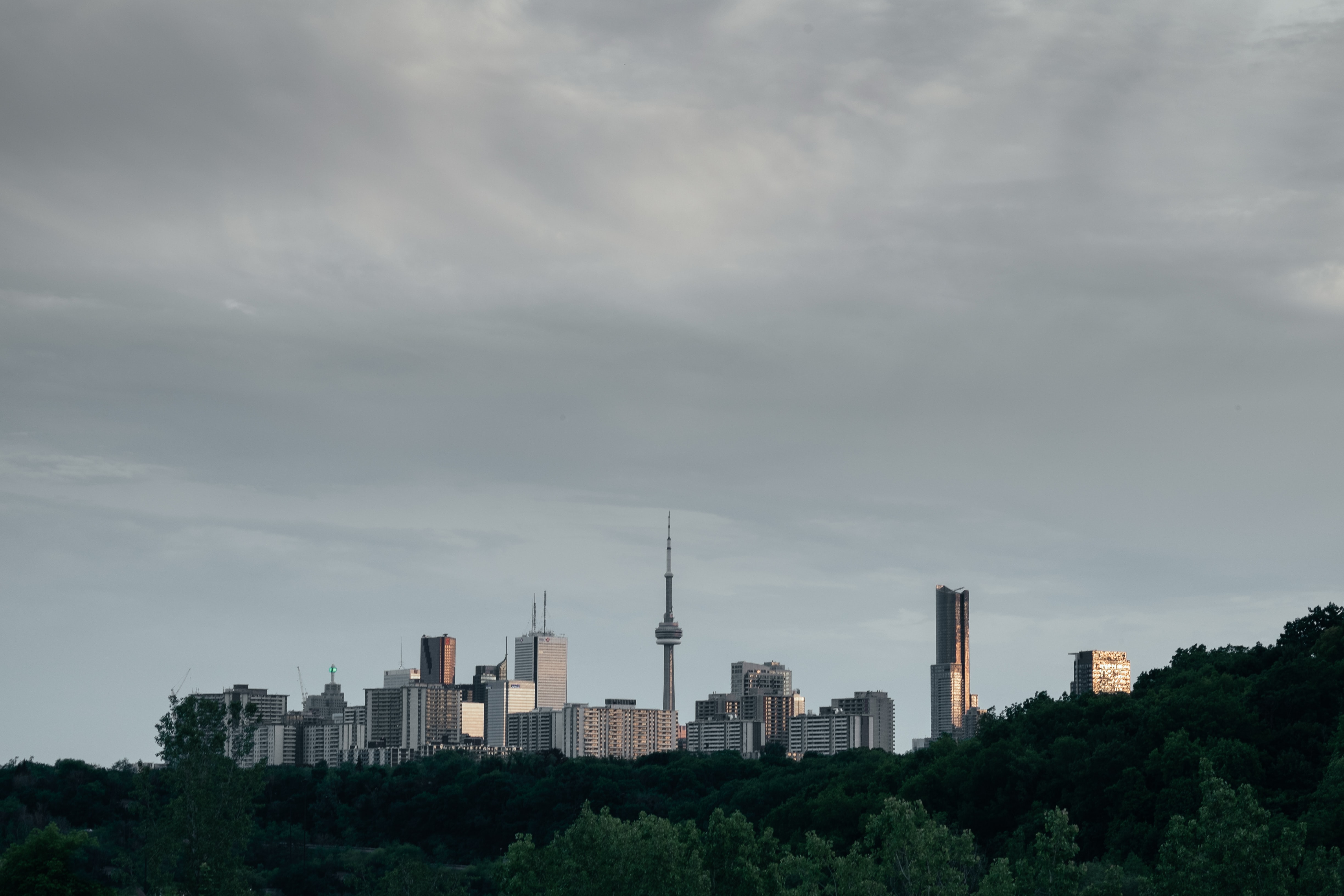 A city skyline with a tall broadcast tower under gray clouds