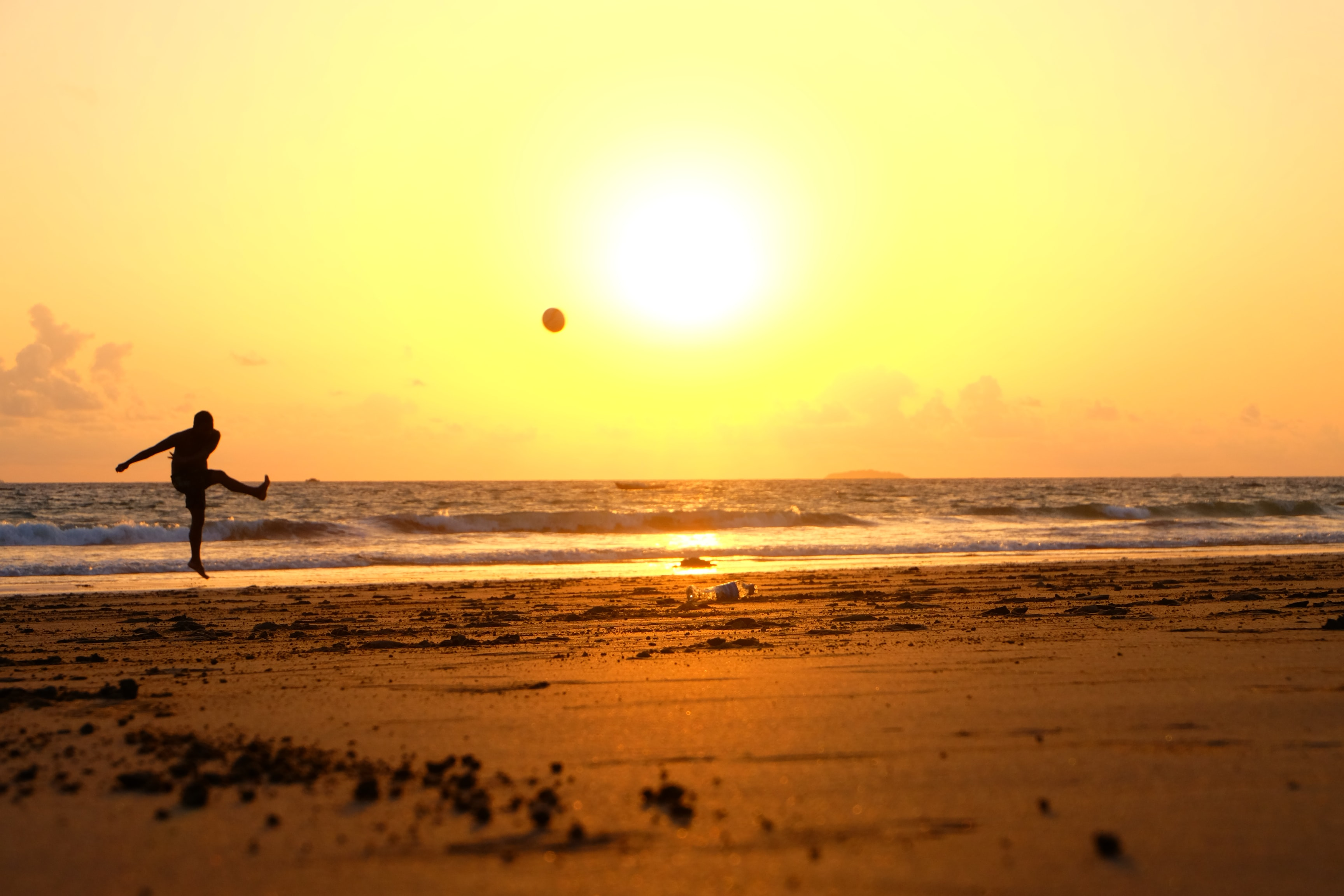 Silhouette kicking the ball in mid air before sunset at the beach in Ngwesaung