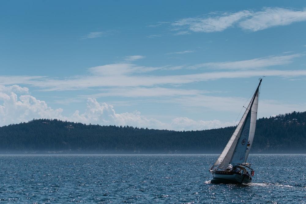black sailboat on sea under blue sky during daytime