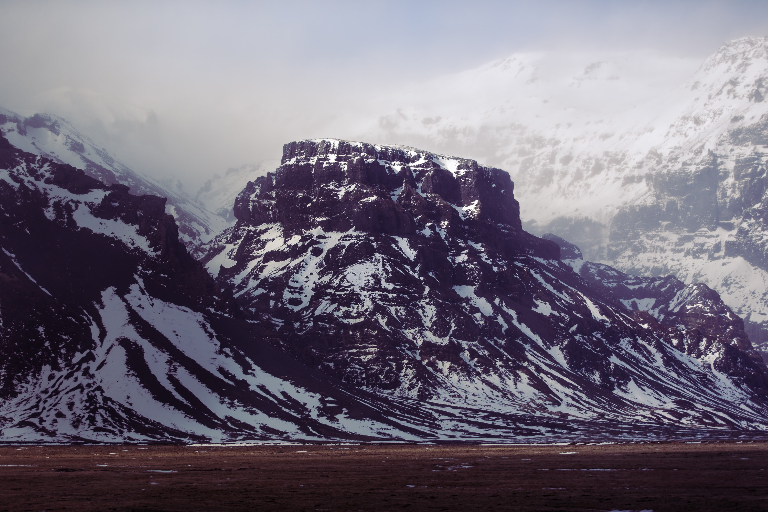 A flat mountain peak in the snow among other snowy mountain ridges