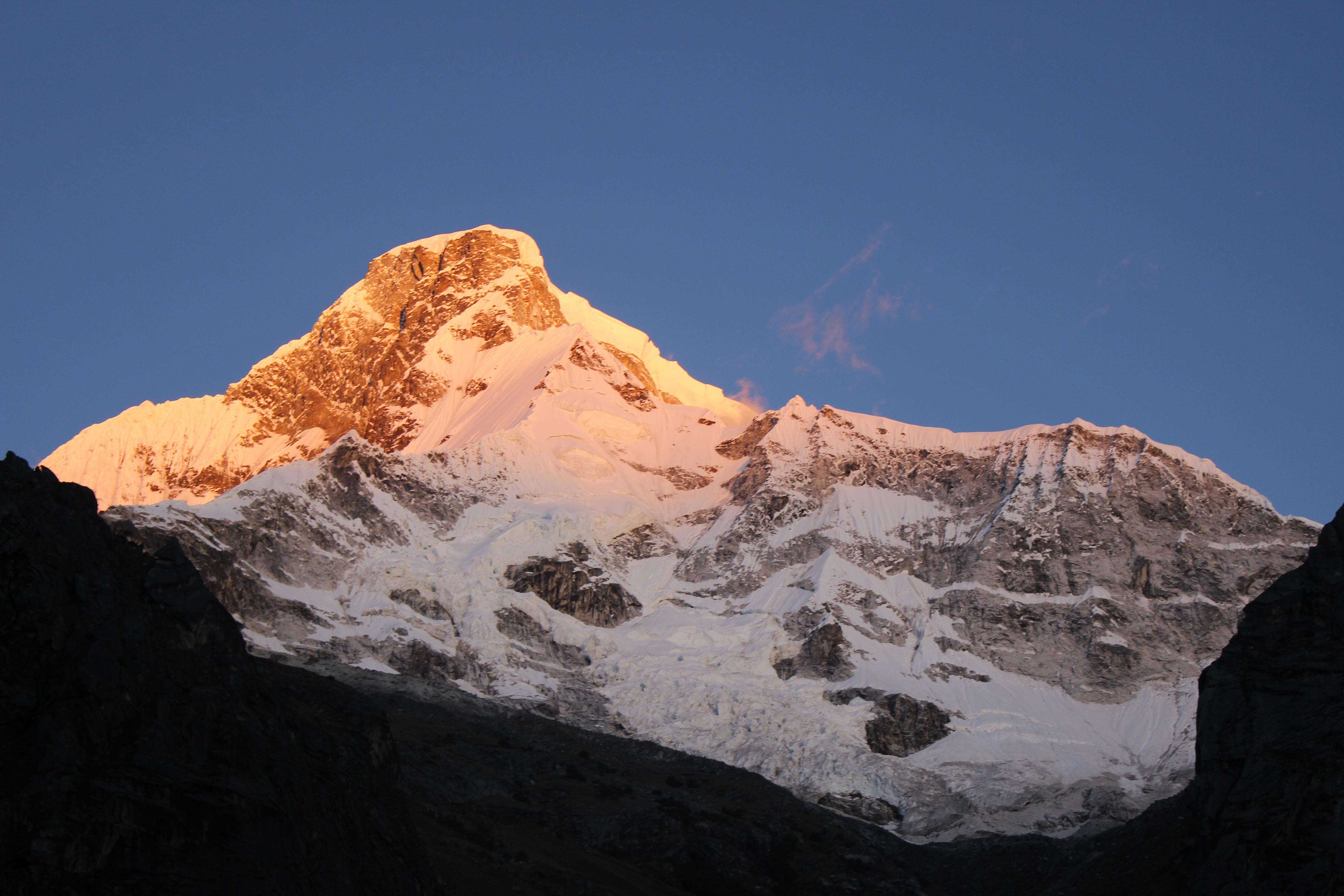 The golden sunlight highlights a snowy mountain peak against a blue sky