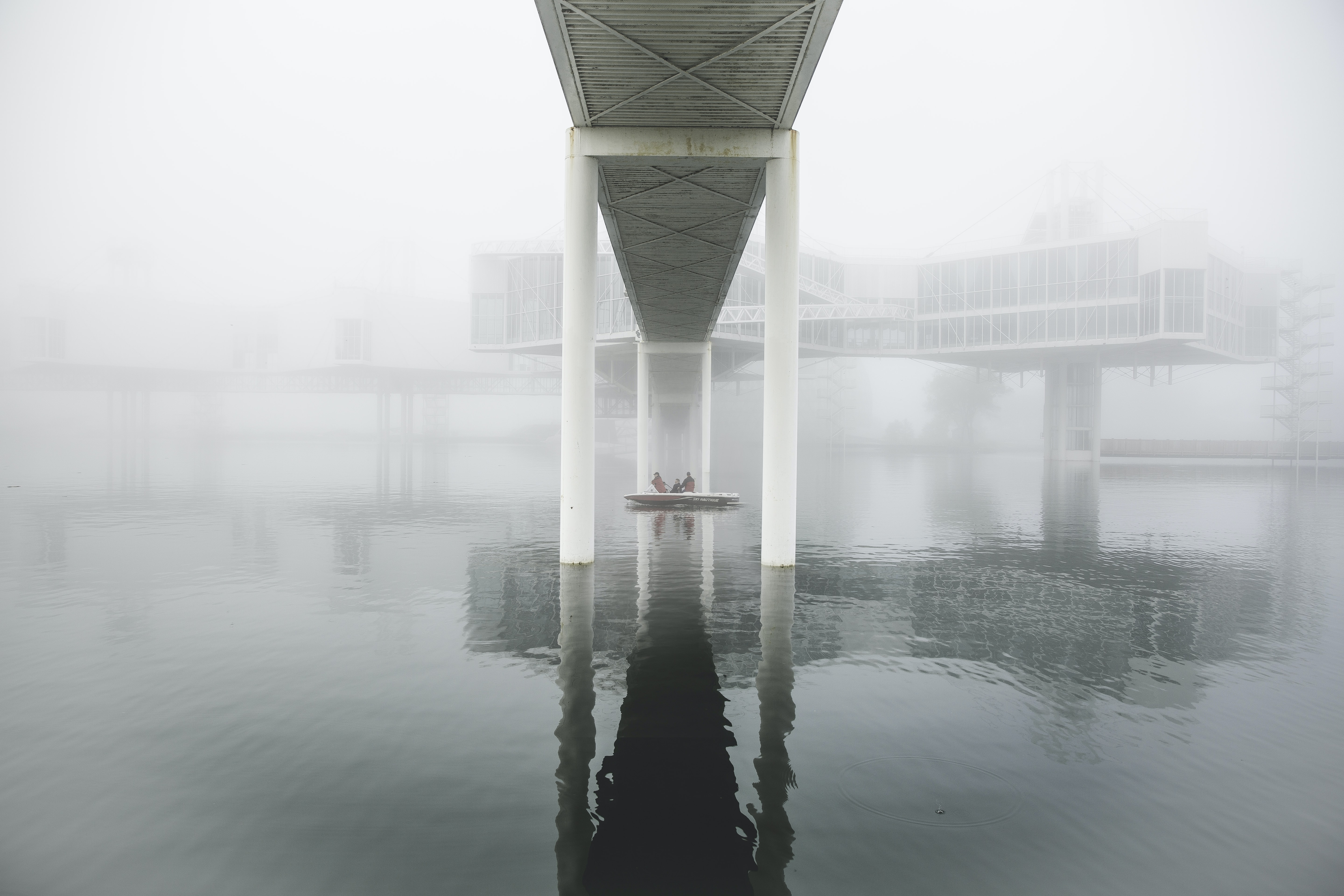 Boat passes under a bridge on a foggy morning at sea