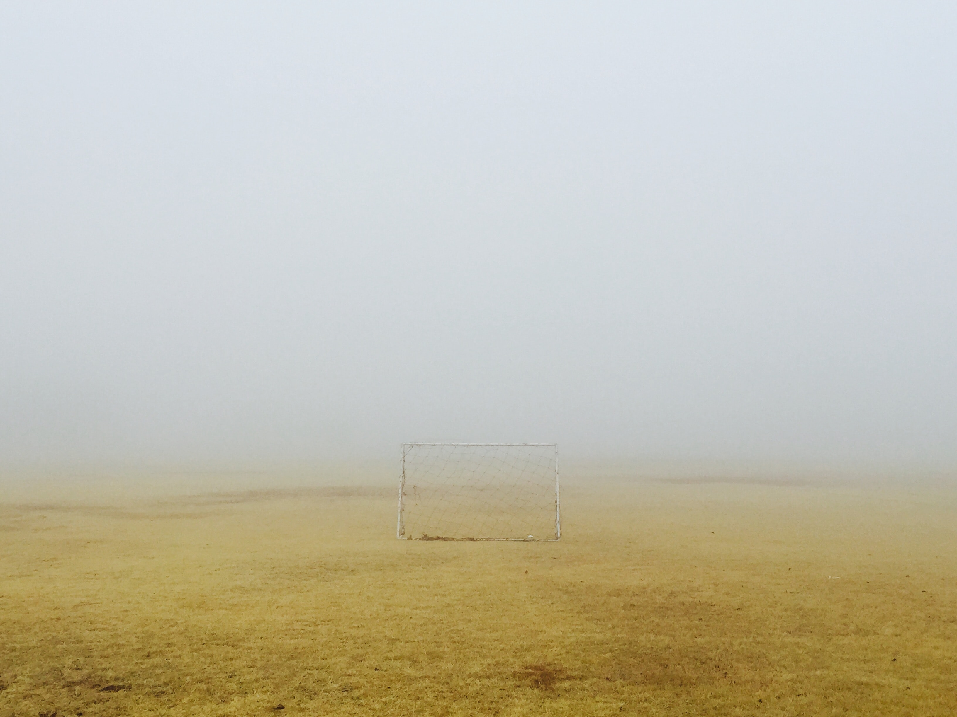 Small soccer goal sitting on the yellow scorched grass field on a foggy day