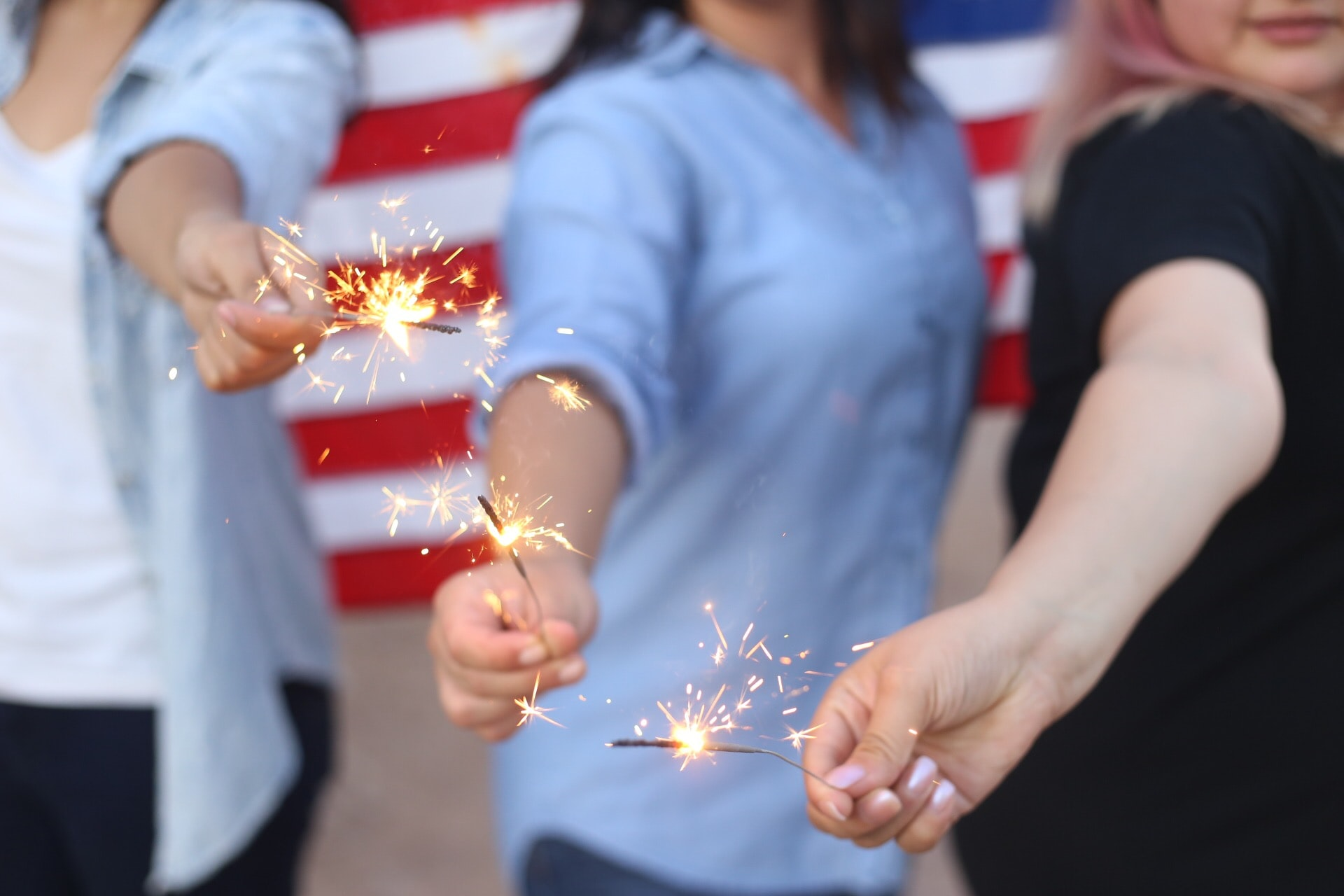 A group of women standing in front of an American flag holding out sparklers