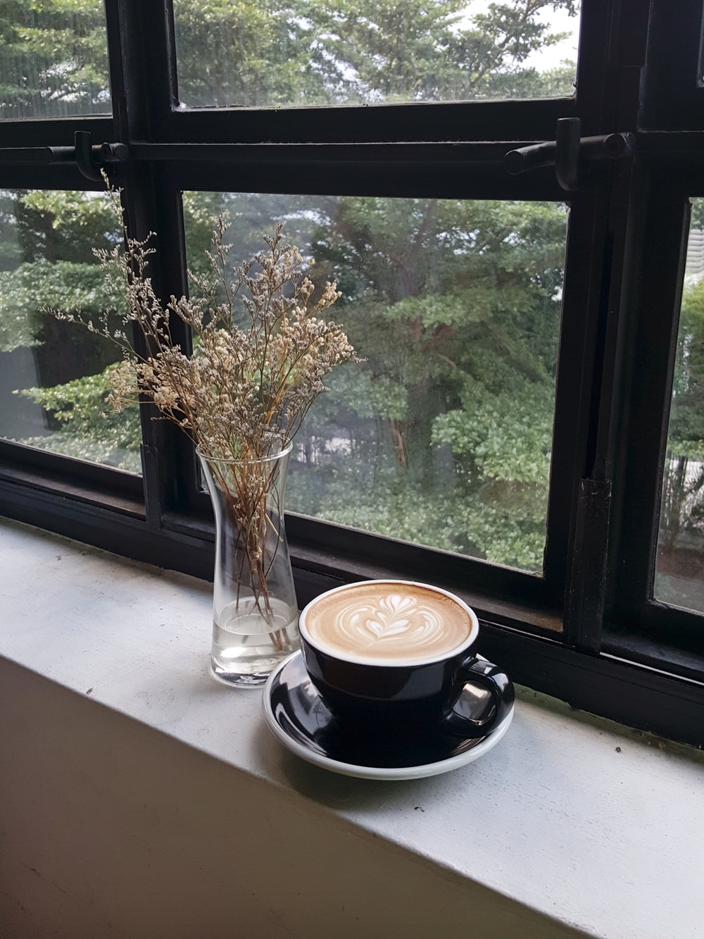 black ceramic coffee mug on window