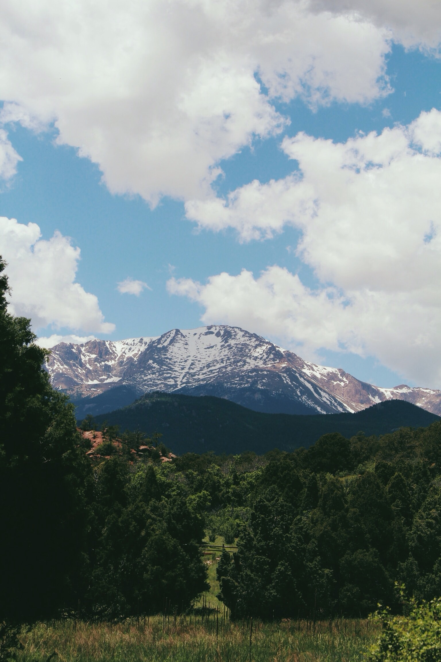 A tall snowy mountain towering over green countryside
