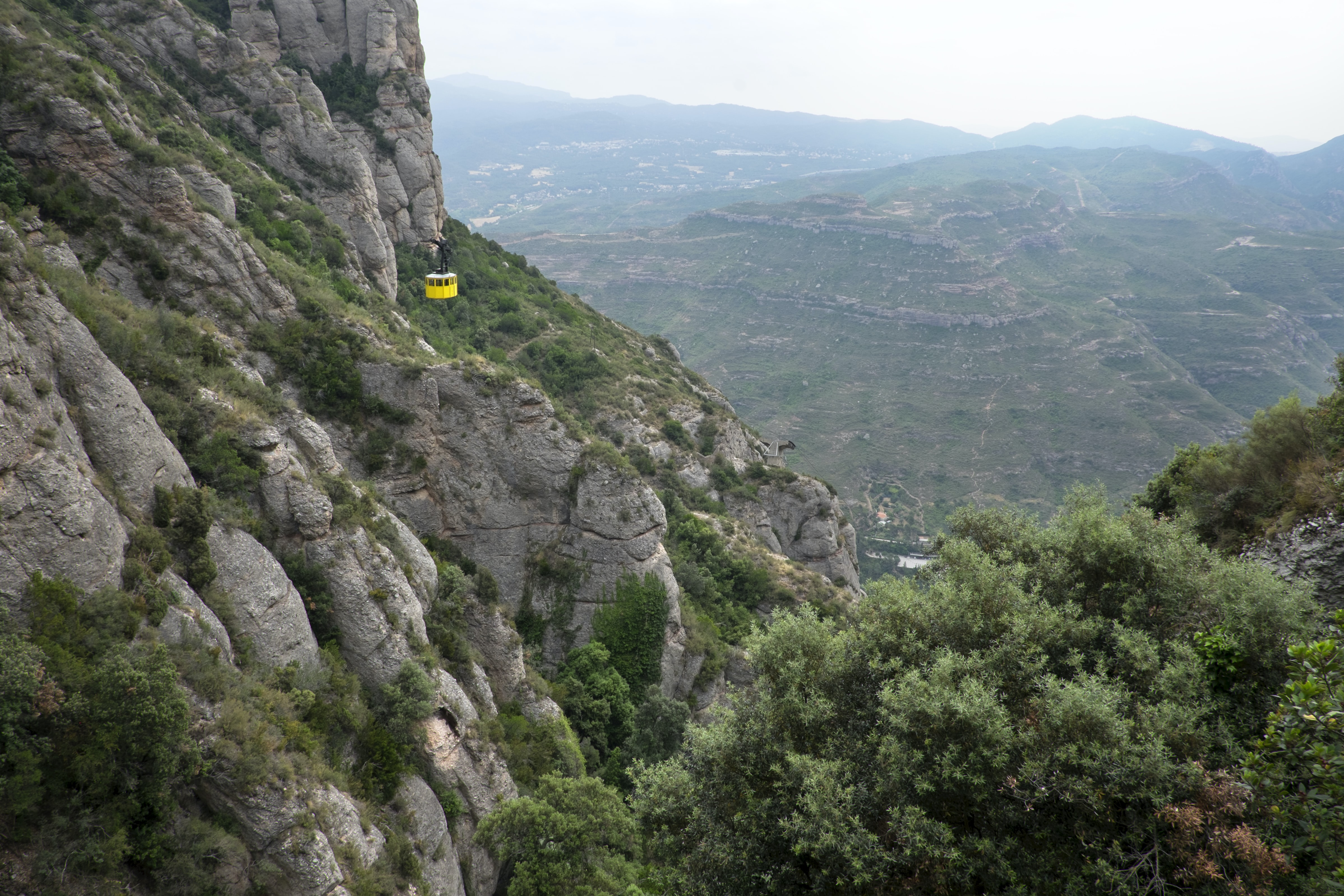Long shot of yellow cable car travelling through mountain valley with vegetation