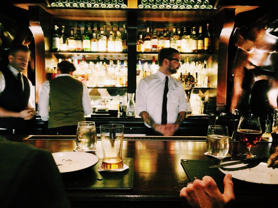 bartender standing behind a wooden bar