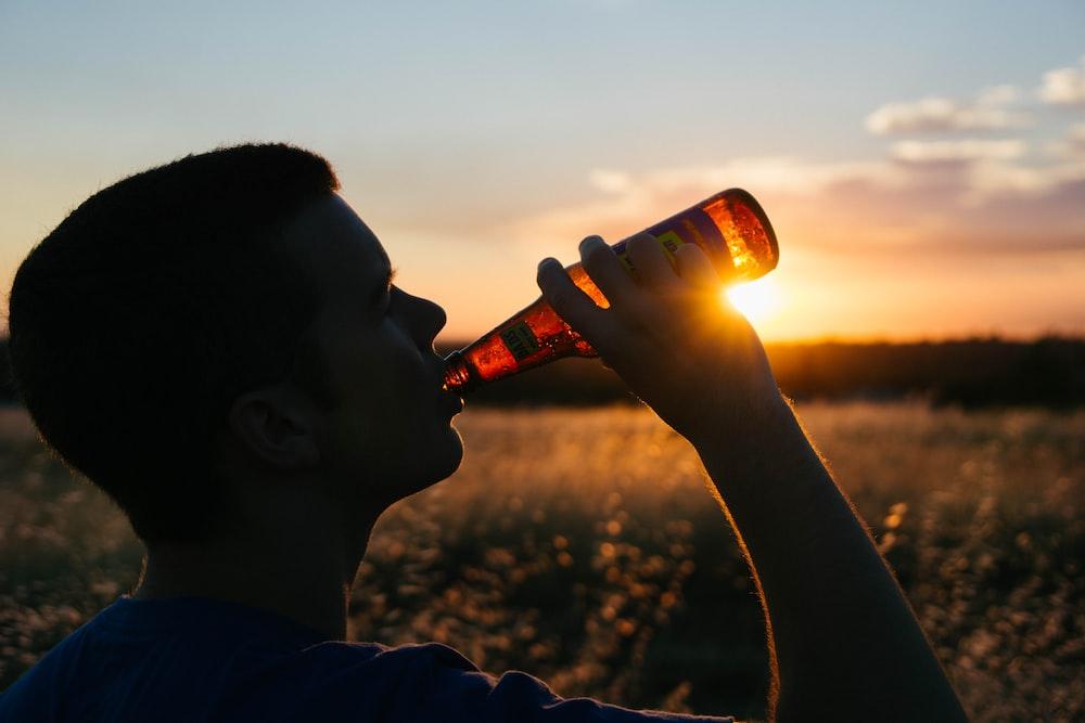 man holding glass bottle