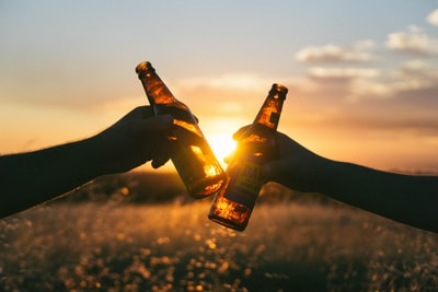 photography of person holding glass bottles during sunset cider zoom background